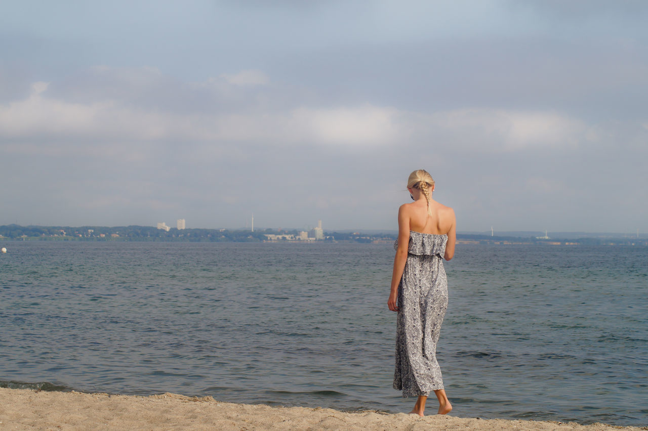 Rear View Of Woman Walking On Shore At Beach Against Sky