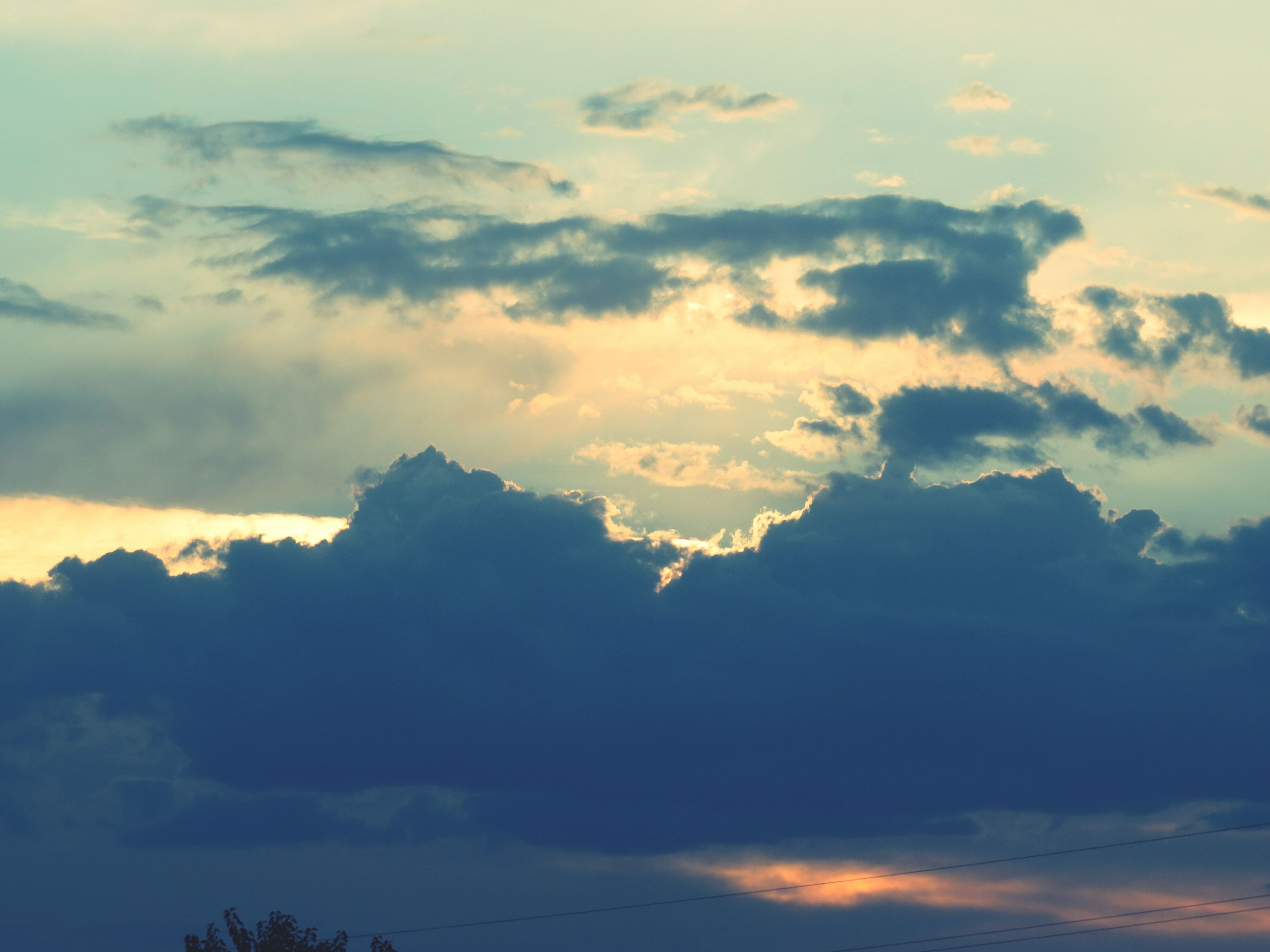 sky, cloud - sky, scenics, beauty in nature, tranquility, tranquil scene, low angle view, cloudy, nature, cloudscape, sunset, sky only, idyllic, cloud, weather, majestic, dramatic sky, silhouette, outdoors, no people