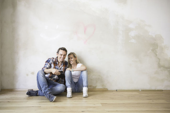 Young couple relaxing on a wooden floor. Casual Clothing Computer Day Happiness Hardwood Floor Heart Leisure Activity Lifestyles Relaxation Renovations Sitting