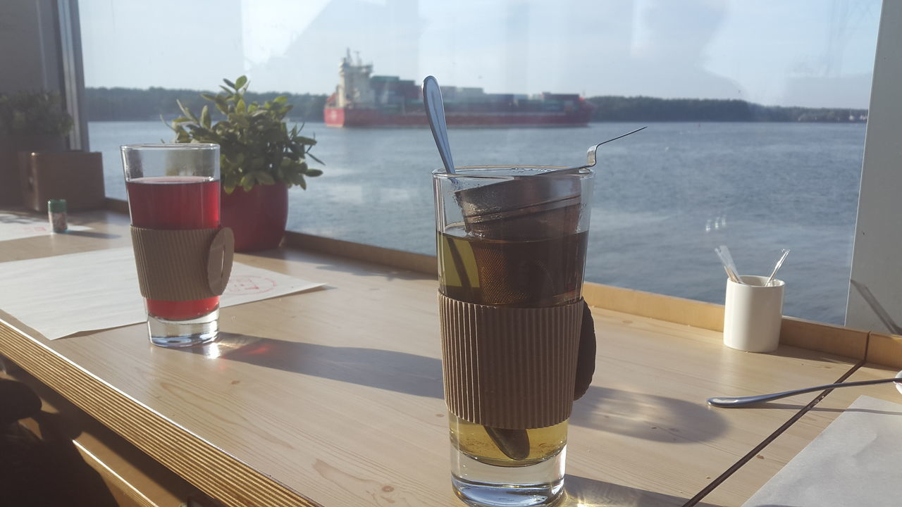 Drink In Glasses On Table By Window During Sunny Day
