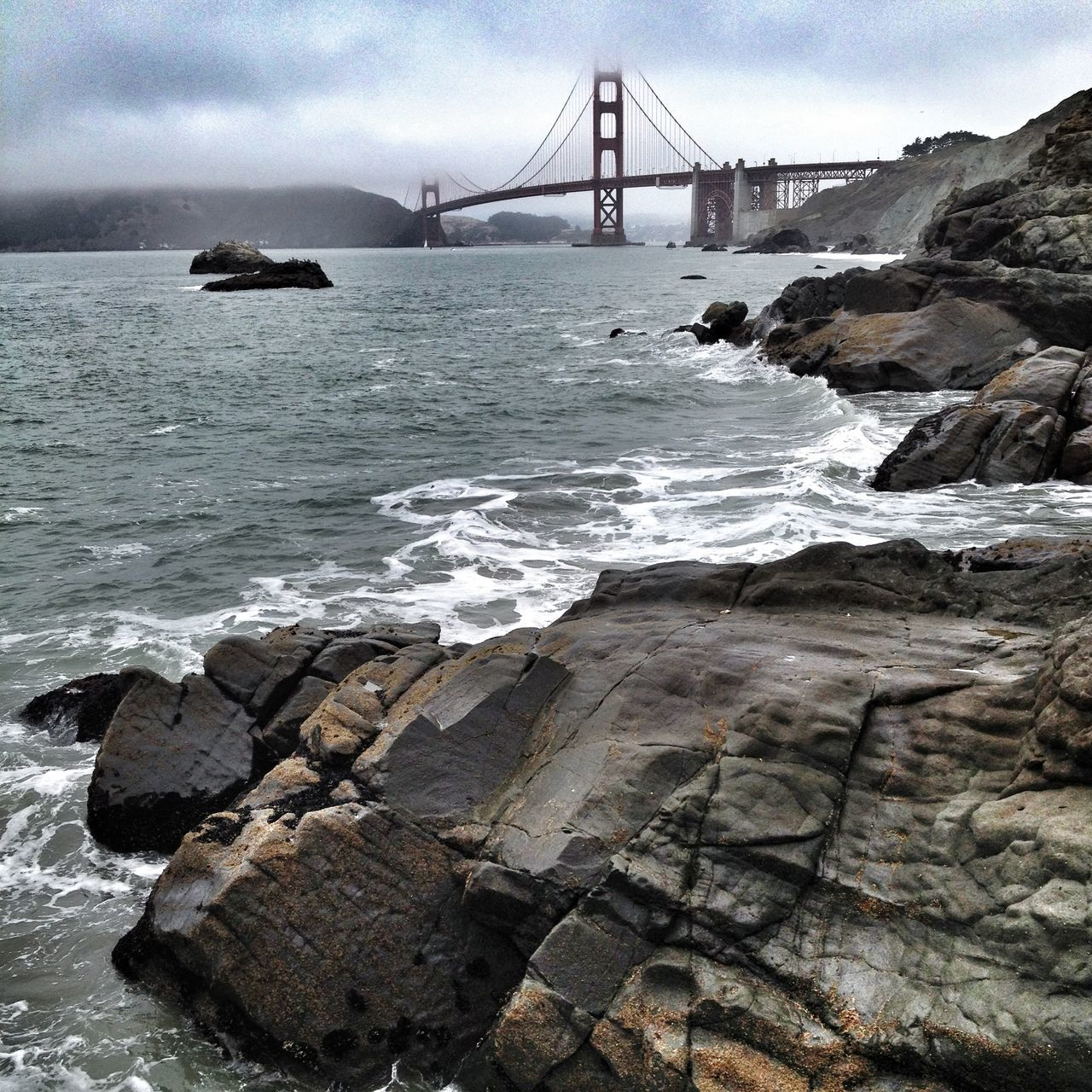 suspension bridge, bridge - man made structure, engineering, connection, travel destinations, tourism, architecture, travel, sea, bridge, water, transportation, built structure, outdoors, sky, rock - object, nature, no people, day, city, beauty in nature
