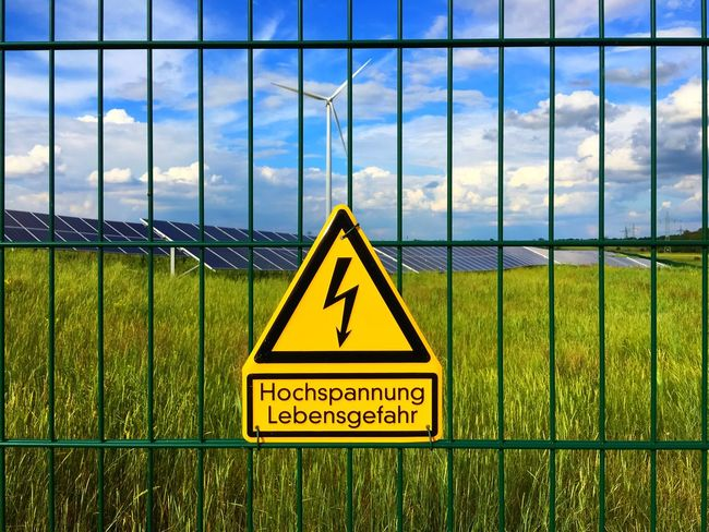 fence with high voltage sign and solar plant in the background Chainlink Fence Cloud Cloud - Sky Cloudy Danger Fence Focus On Foreground Grass Grass Grassy Green High Voltage High Voltage Sign Nature Sign Solar Solar Energy Solar Energy Plant Solar Plant Voltage Warning Warning Sign Warningsign Wind Turbine Yellow