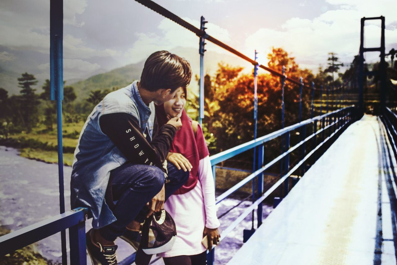 real people, railing, full length, lifestyles, bridge - man made structure, leisure activity, casual clothing, outdoors, young men, young adult, day, nature, footbridge, tree, sky