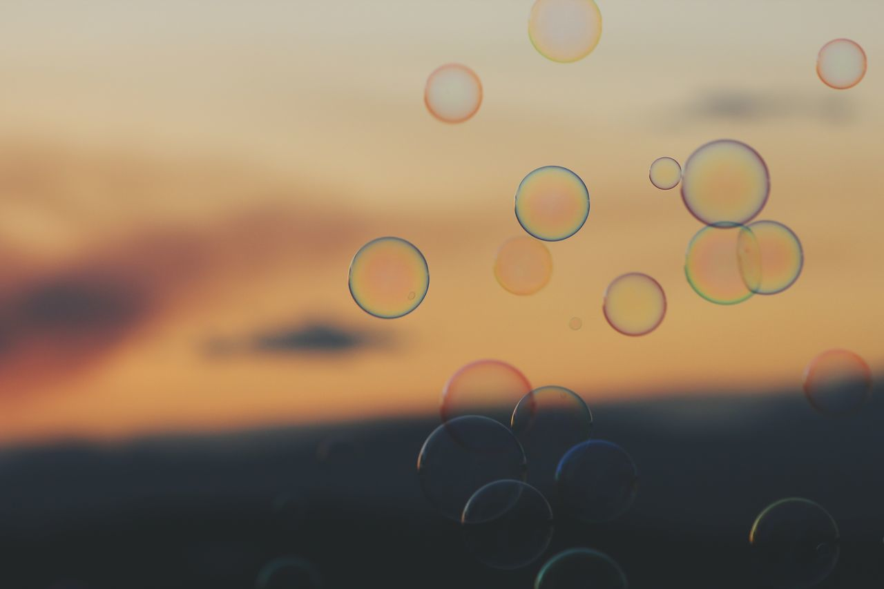 bubble, bubble wand, fragility, shape, drop, sunset, focus on foreground, water, rainbow, close-up, sky, nature, no people, multi colored, outdoors, spectrum, day, beauty in nature, freshness
