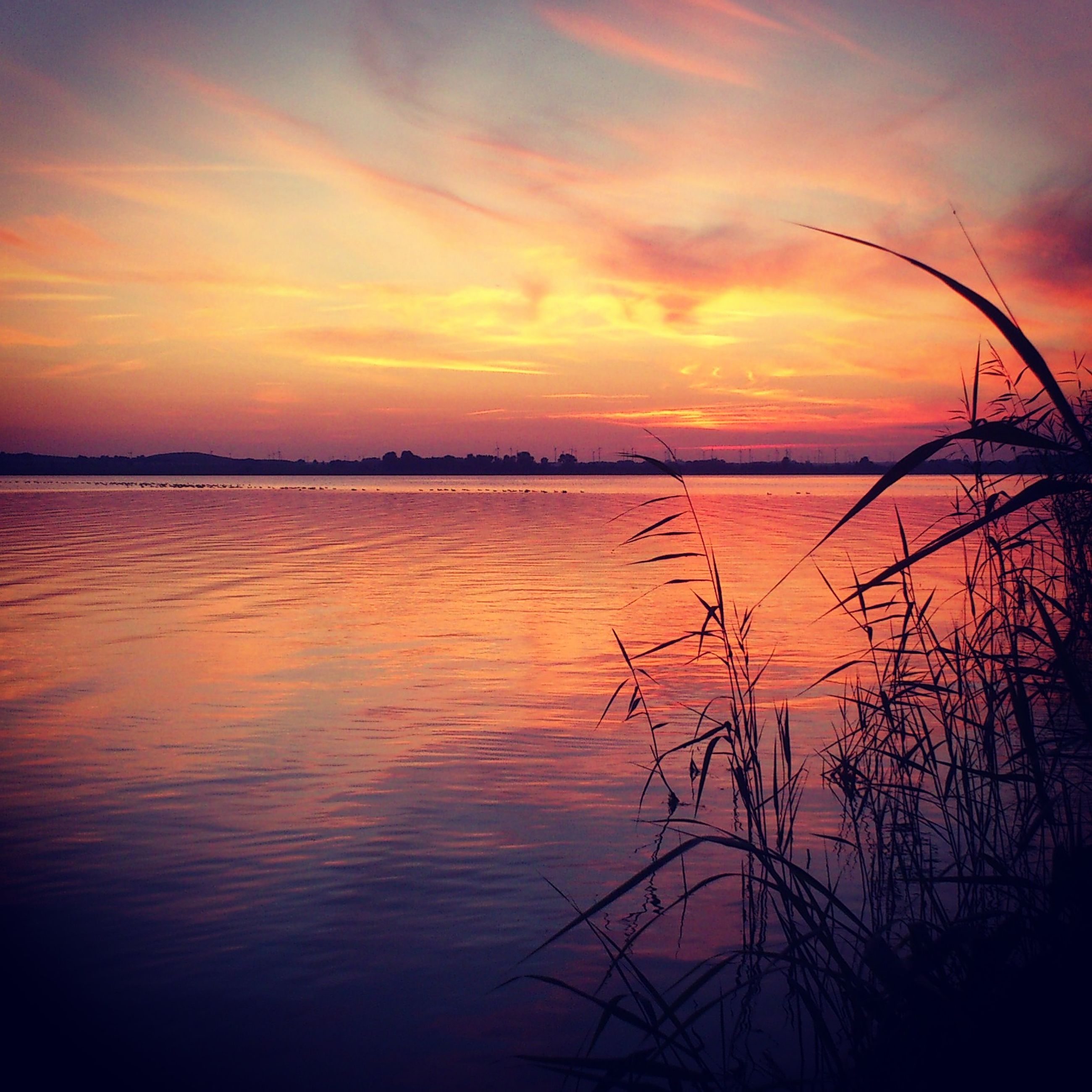 sunset, water, tranquil scene, orange color, scenics, tranquility, silhouette, sky, beauty in nature, reflection, idyllic, lake, nature, cloud - sky, dramatic sky, majestic, cloud, sun, outdoors, moody sky