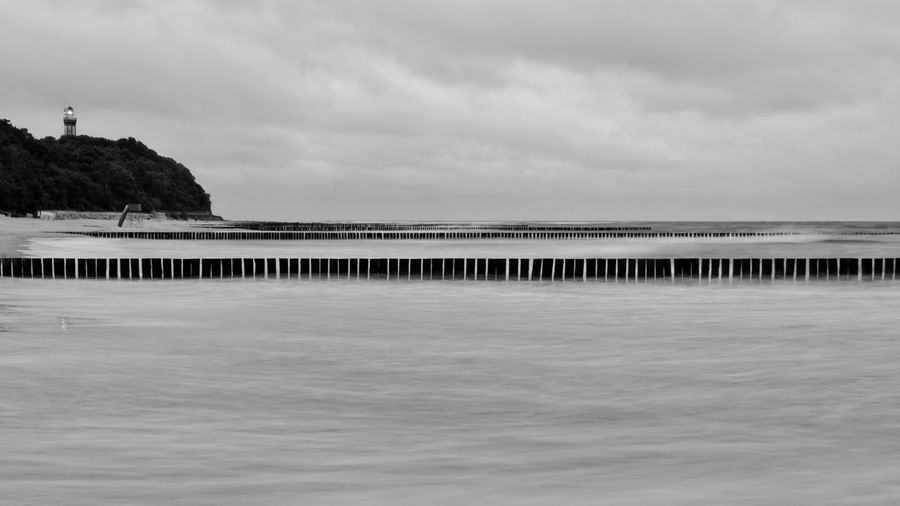 Wooden breakwater near lighthouse in Niechorze (Poland) shot at dawn with long exposure. Autumn Baltic Sea Empty Beach Lighthouse Rough Sea Beach Beauty In Nature Black And White Breakwater Cloud - Sky Cold Atmosphere Day Long Exposure Mystery Nature No People Outdoors Scenics Sea Sea At Dawn Sky Tranquil Scene Tranquility Water Waves