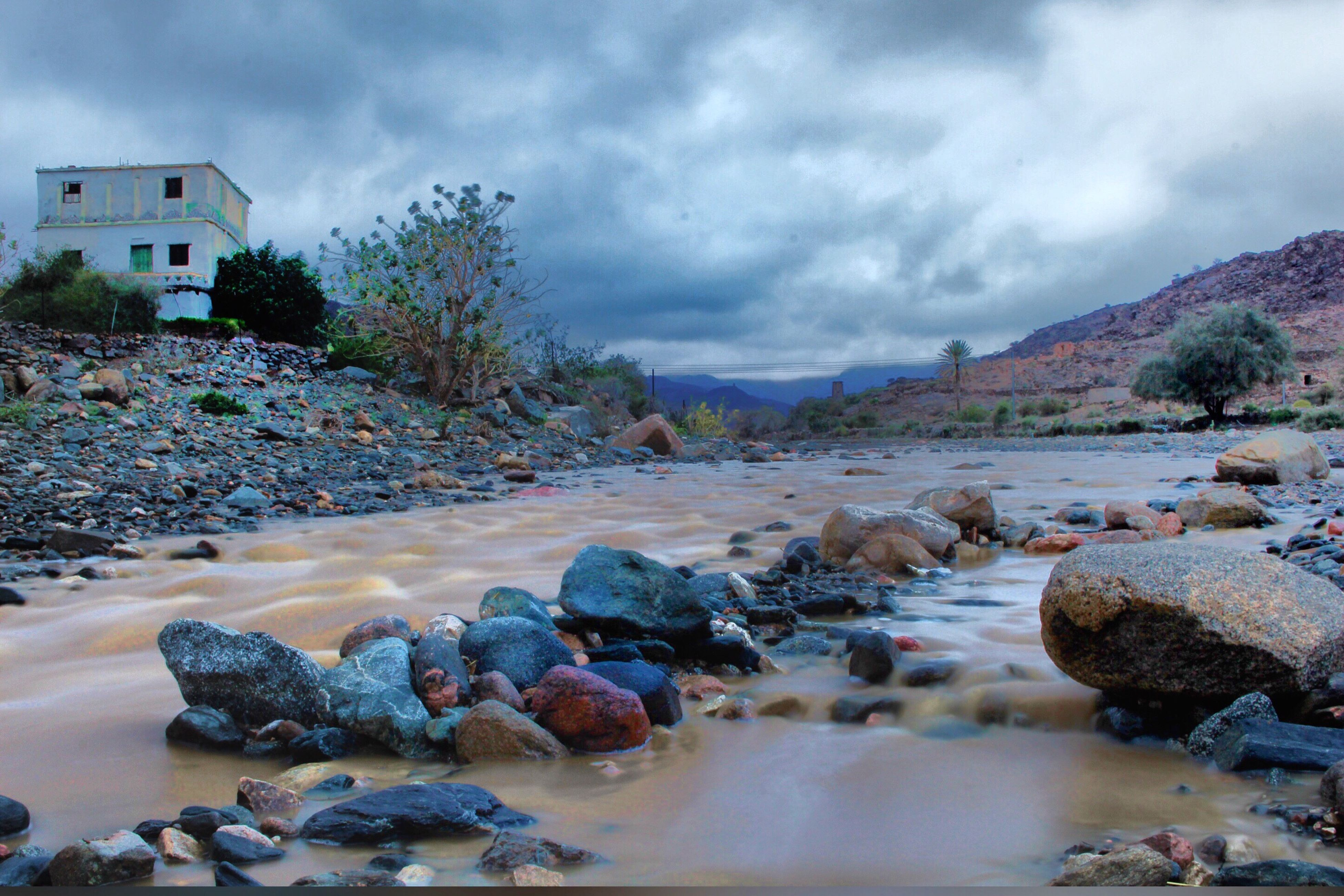 water, rock - object, cloud - sky, river, architecture, scenics, built structure, flowing, stone - object, non-urban scene, building exterior, stream, sky, tranquil scene, travel destinations, overcast, tranquility, nature, tourism, cloudy, cloud, beauty in nature, flowing water, stone, outdoors, riverbank, day, rock, no people