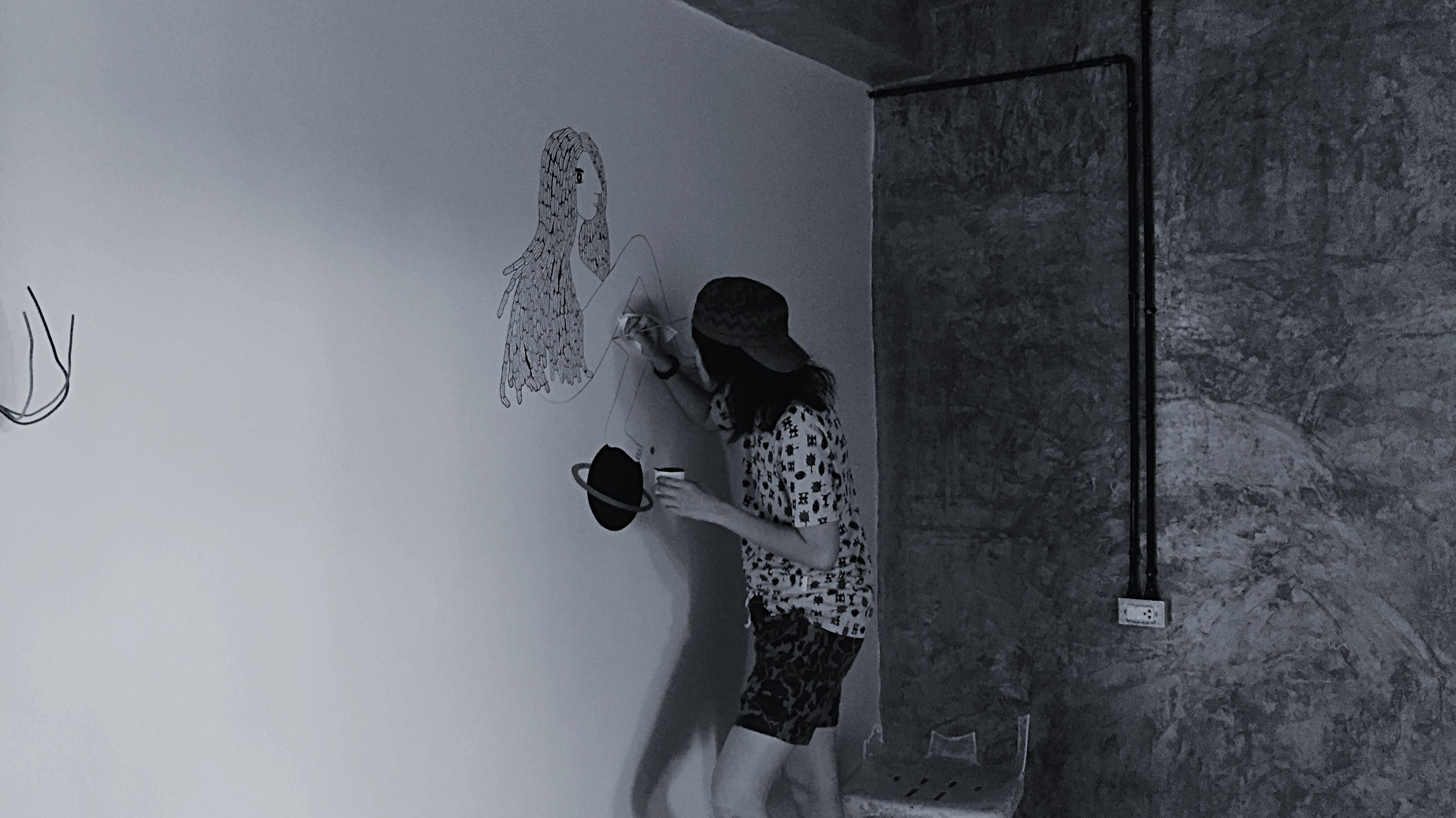 wall - building feature, low angle view, human representation, copy space, art, person, art and craft, lifestyles, creativity, shadow, men, holding, leisure activity, unrecognizable person, wall, animal representation, indoors, day