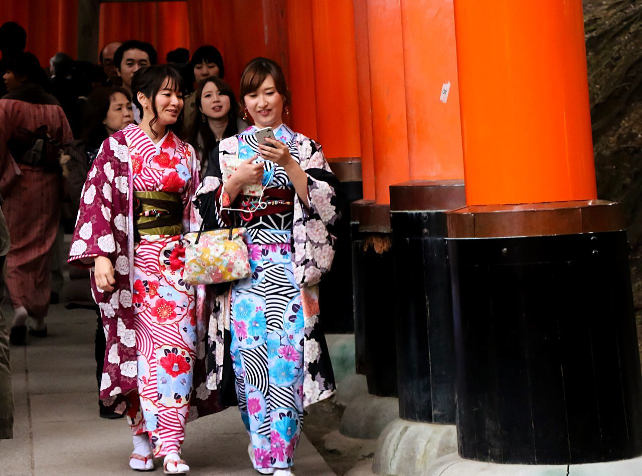 smiling, real people, traditional clothing, lifestyles, happiness, togetherness, selfie, leisure activity, looking at camera, young women, full length, beautiful woman, outdoors, portrait, women, young adult, standing, day, kimono, friendship, photo messaging, wireless technology, technology, photography themes, people