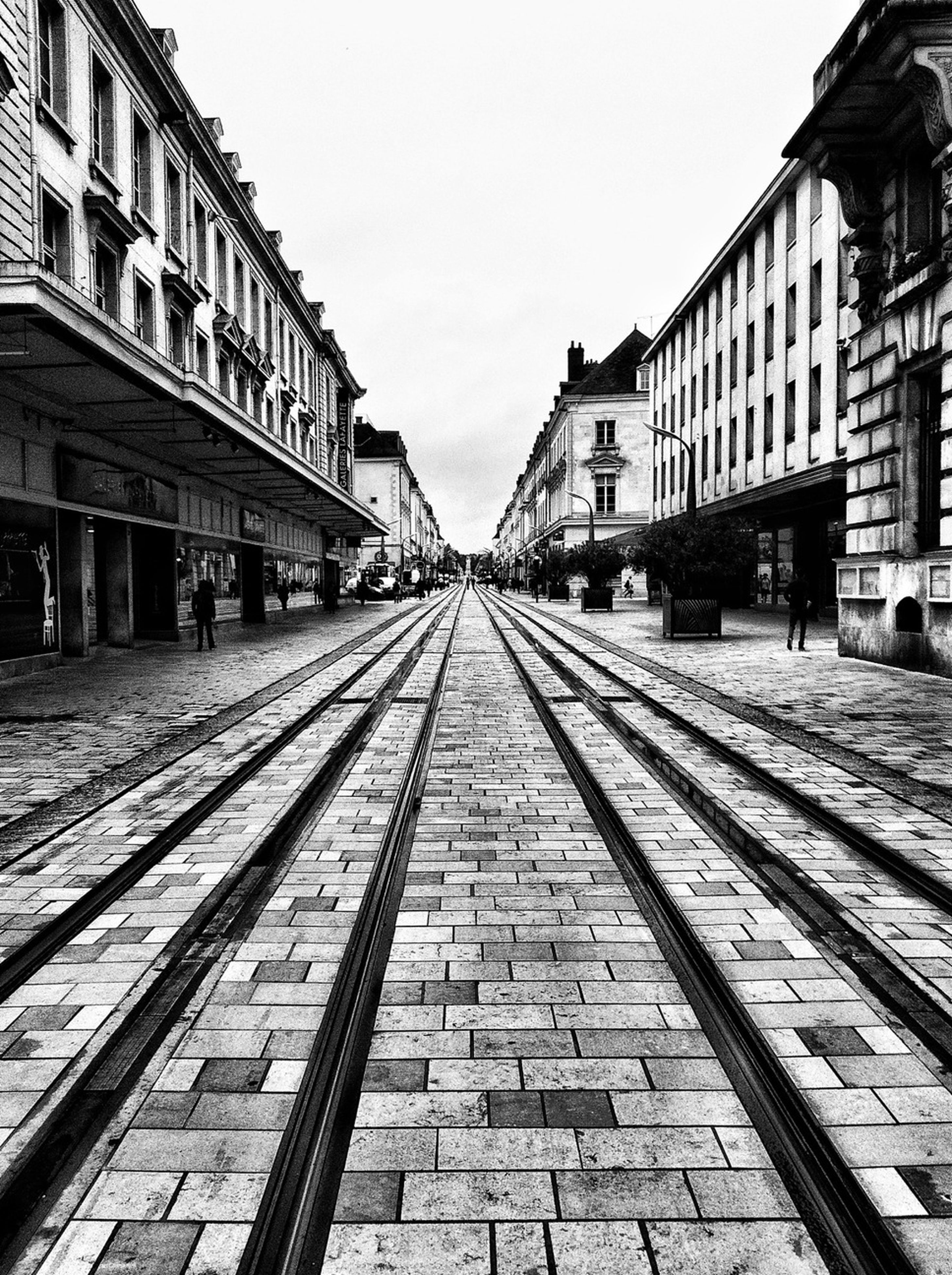 architecture, built structure, building exterior, the way forward, diminishing perspective, vanishing point, railroad track, city, transportation, clear sky, building, sky, incidental people, day, outdoors, street, cobblestone, rail transportation, residential building, empty