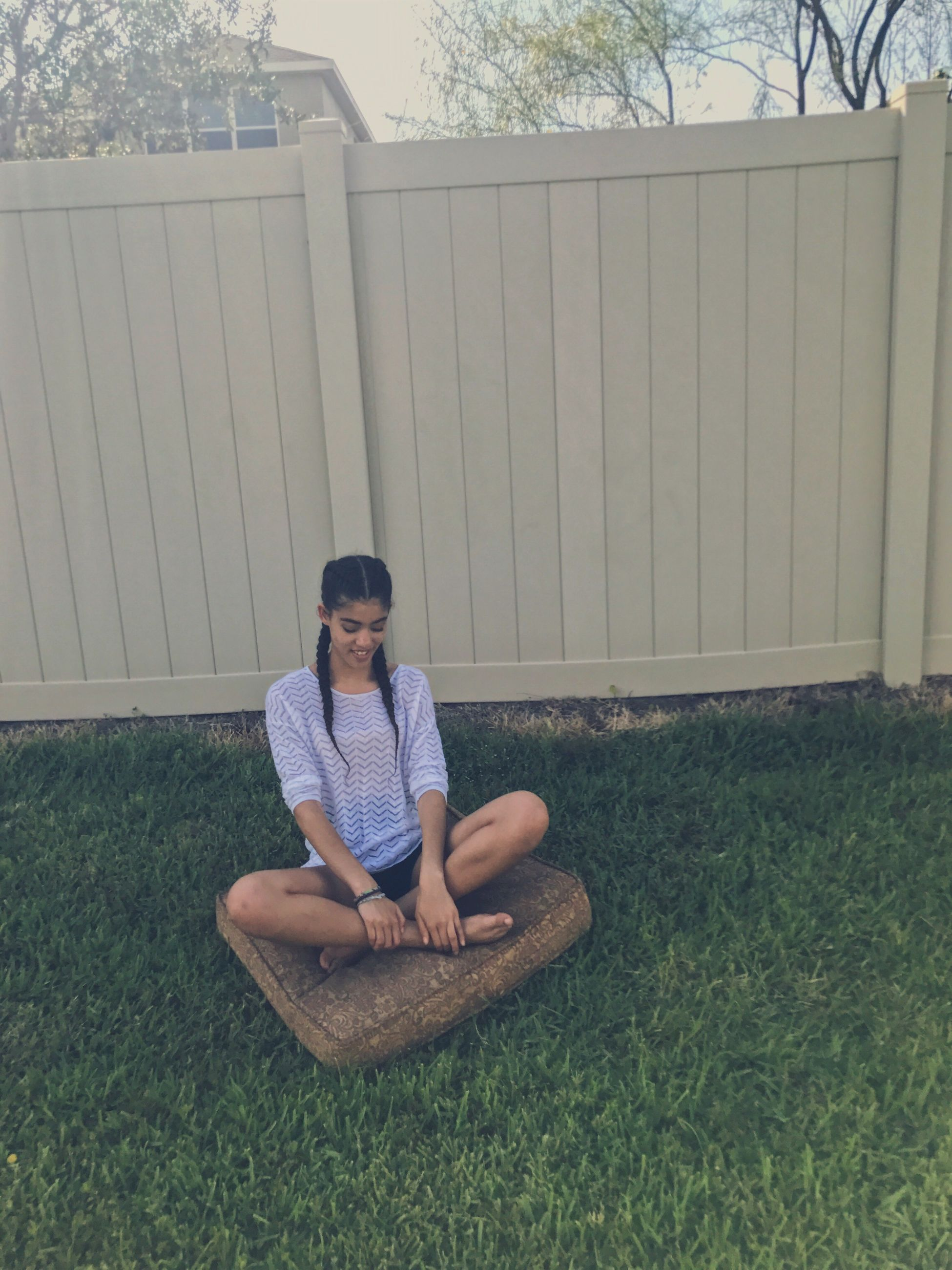 sitting, full length, front view, casual clothing, grass, smiling, outdoors, day, one person, young adult, lifestyles, real people