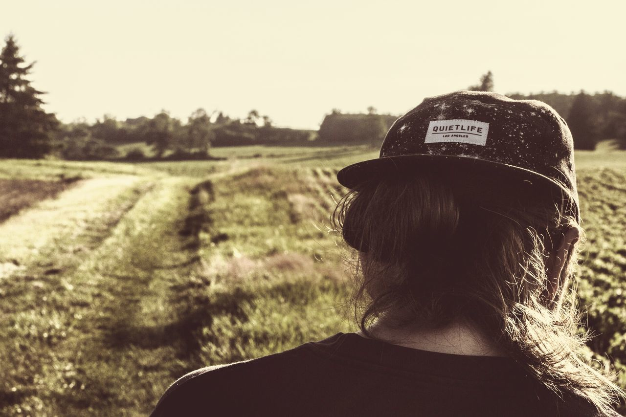 field, rear view, real people, headshot, one person, outdoors, landscape, day, nature, clear sky, rural scene, sky, tree, close-up
