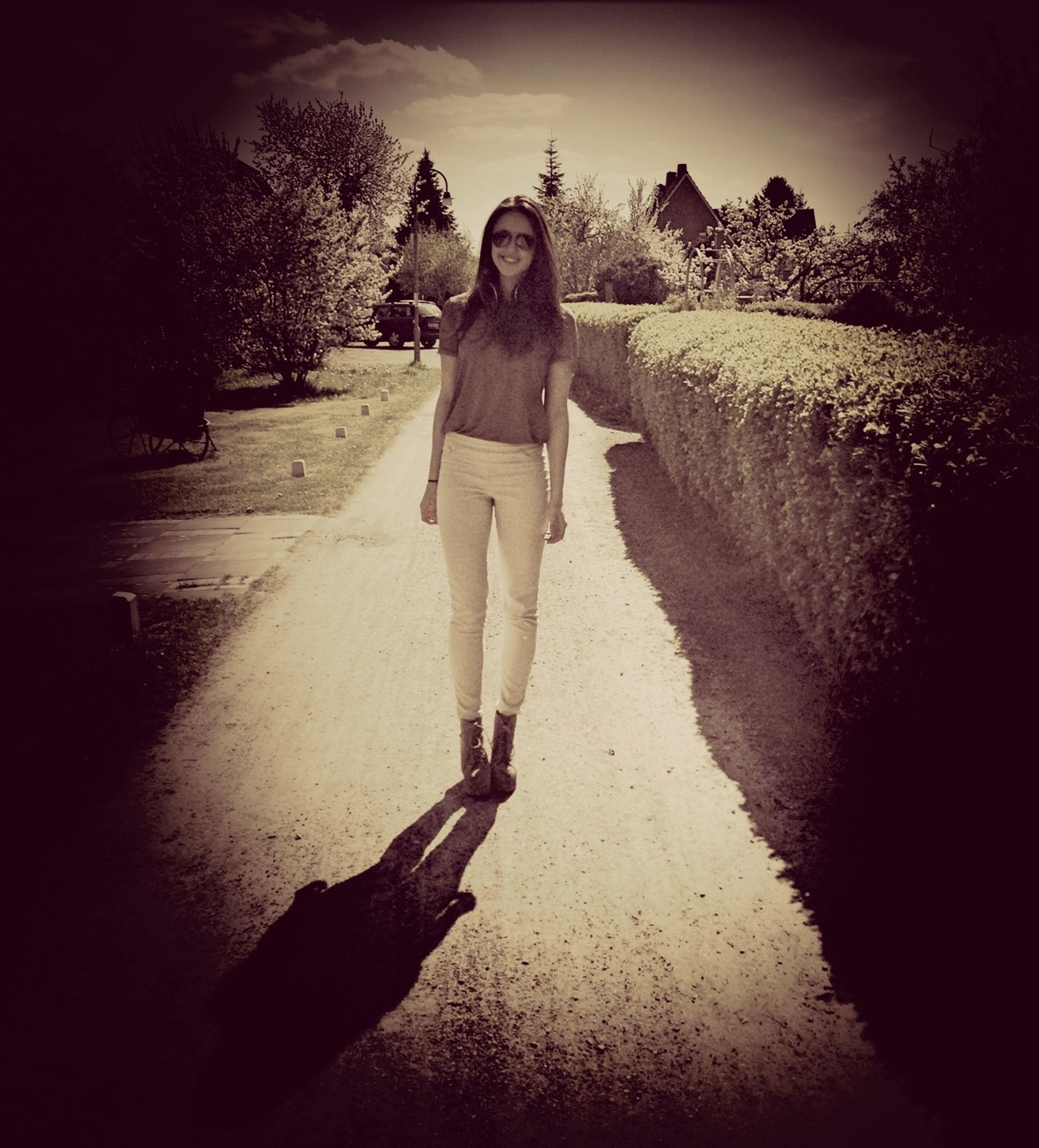 full length, lifestyles, leisure activity, casual clothing, standing, walking, road, shadow, the way forward, tree, rear view, person, young adult, front view, sunlight, day, street, outdoors