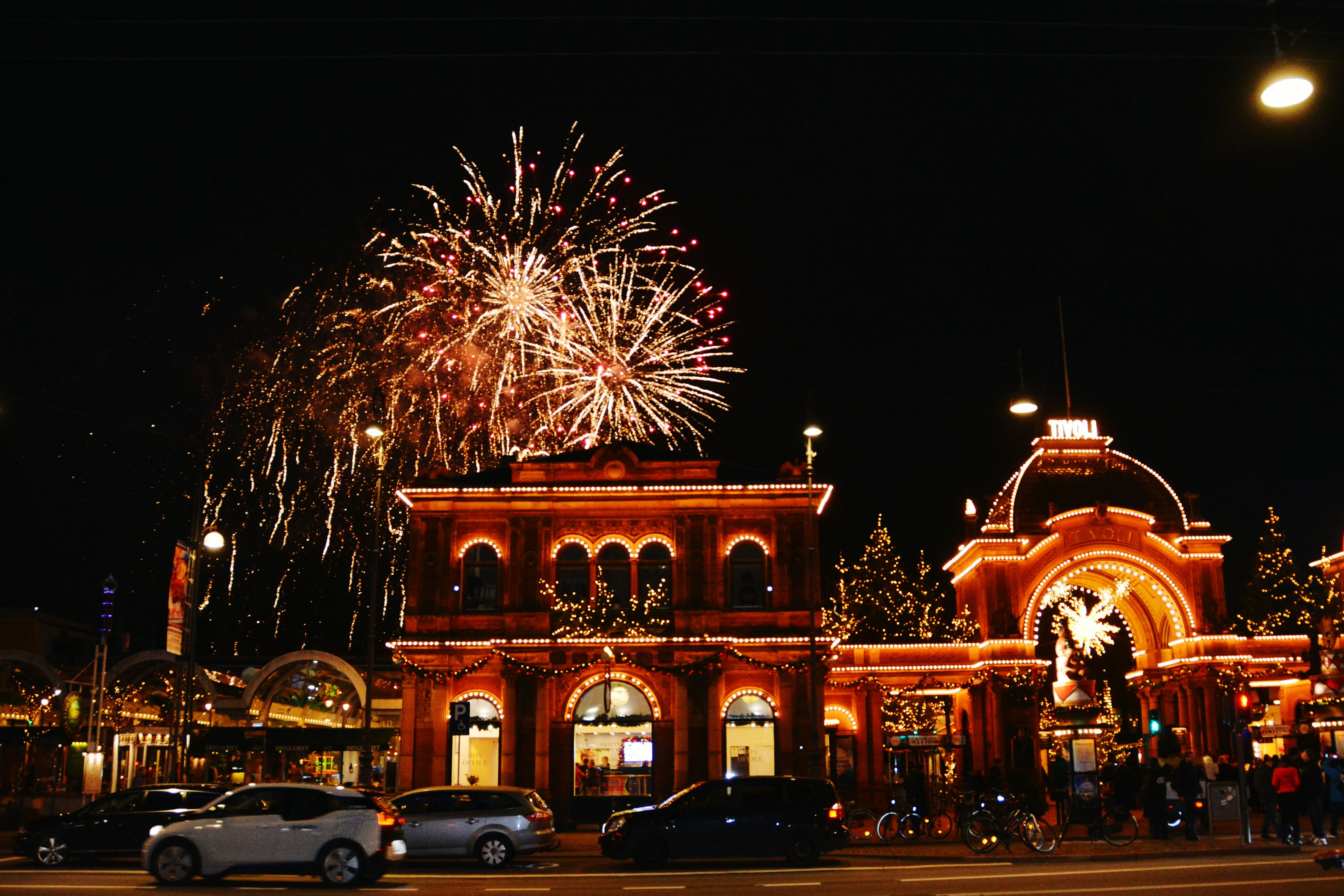 illuminated, night, long exposure, building exterior, car, motion, firework display, land vehicle, street, transportation, arts culture and entertainment, architecture, city, blurred motion, celebration, built structure, mode of transport, glowing, sky, exploding