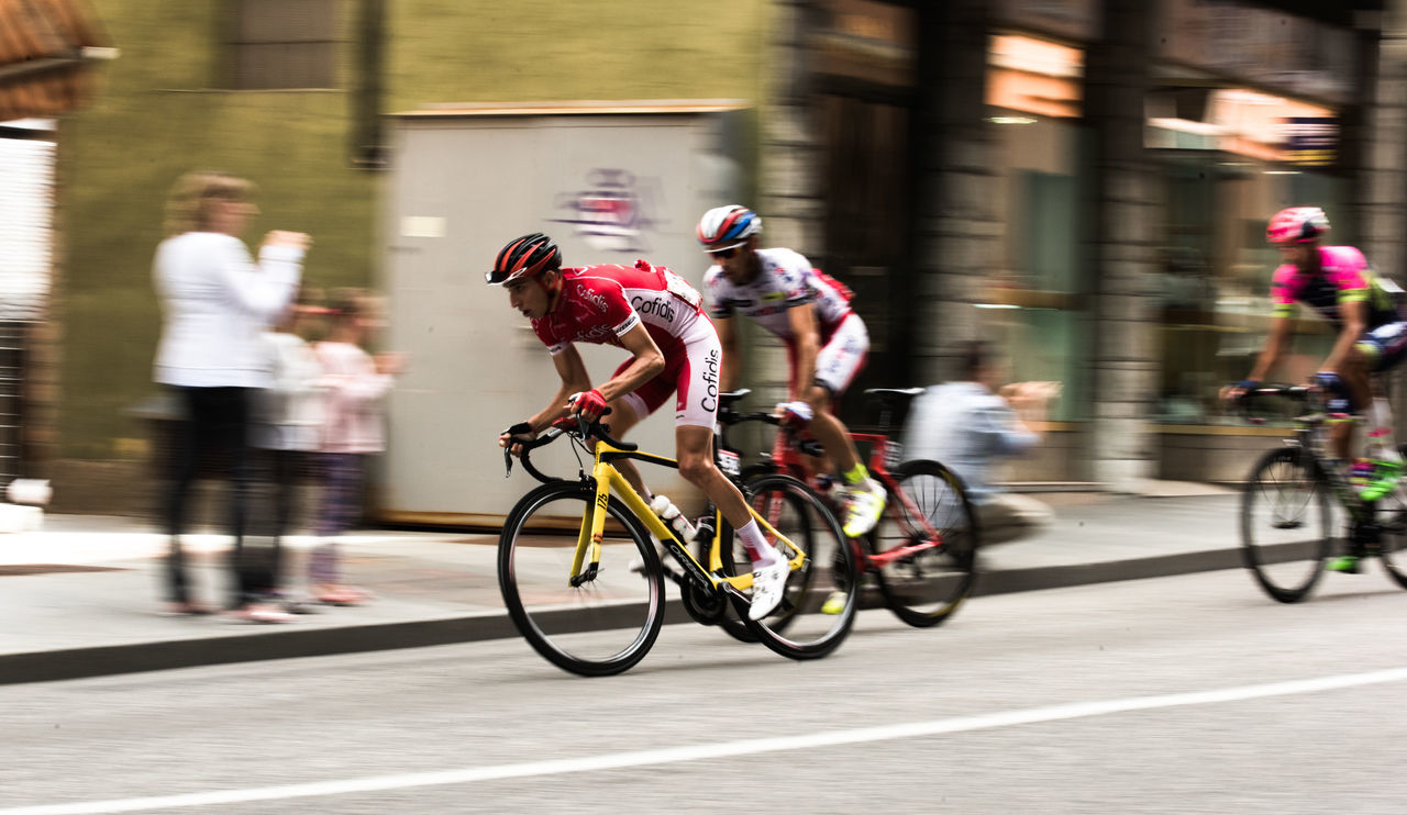 blurred motion, real people, bicycle, motion, mode of transport, men, speed, transportation, riding, street, land vehicle, women, large group of people, road, group of people, outdoors, architecture, competition, day, competitive sport, full length, city