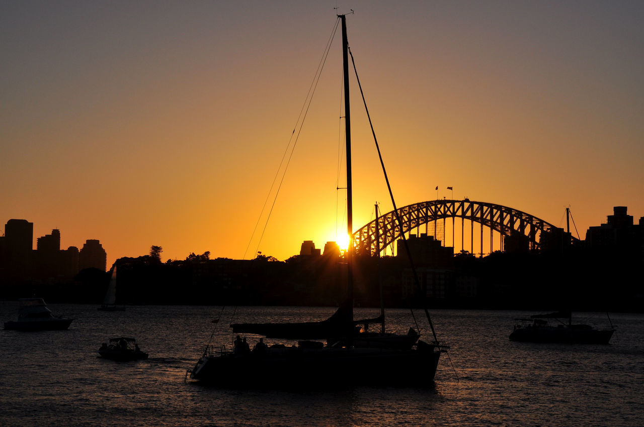sunset, silhouette, architecture, transportation, bridge - man made structure, built structure, water, connection, nautical vessel, sun, river, sky, outdoors, travel destinations, city, clear sky, nature, building exterior, no people, day