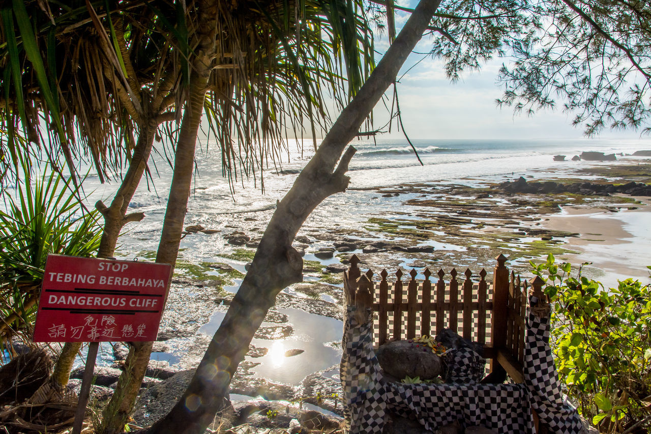 Bali, Indonesia Beach Cliff Danger Sign Day Horizontal Low Tide Nature No People Outdoors Palm Tree Religion Rocks Scenics Sea Sky Sun Beams Sunlight Sunny Temple Travel Destinations Tree Trees Vacations Water