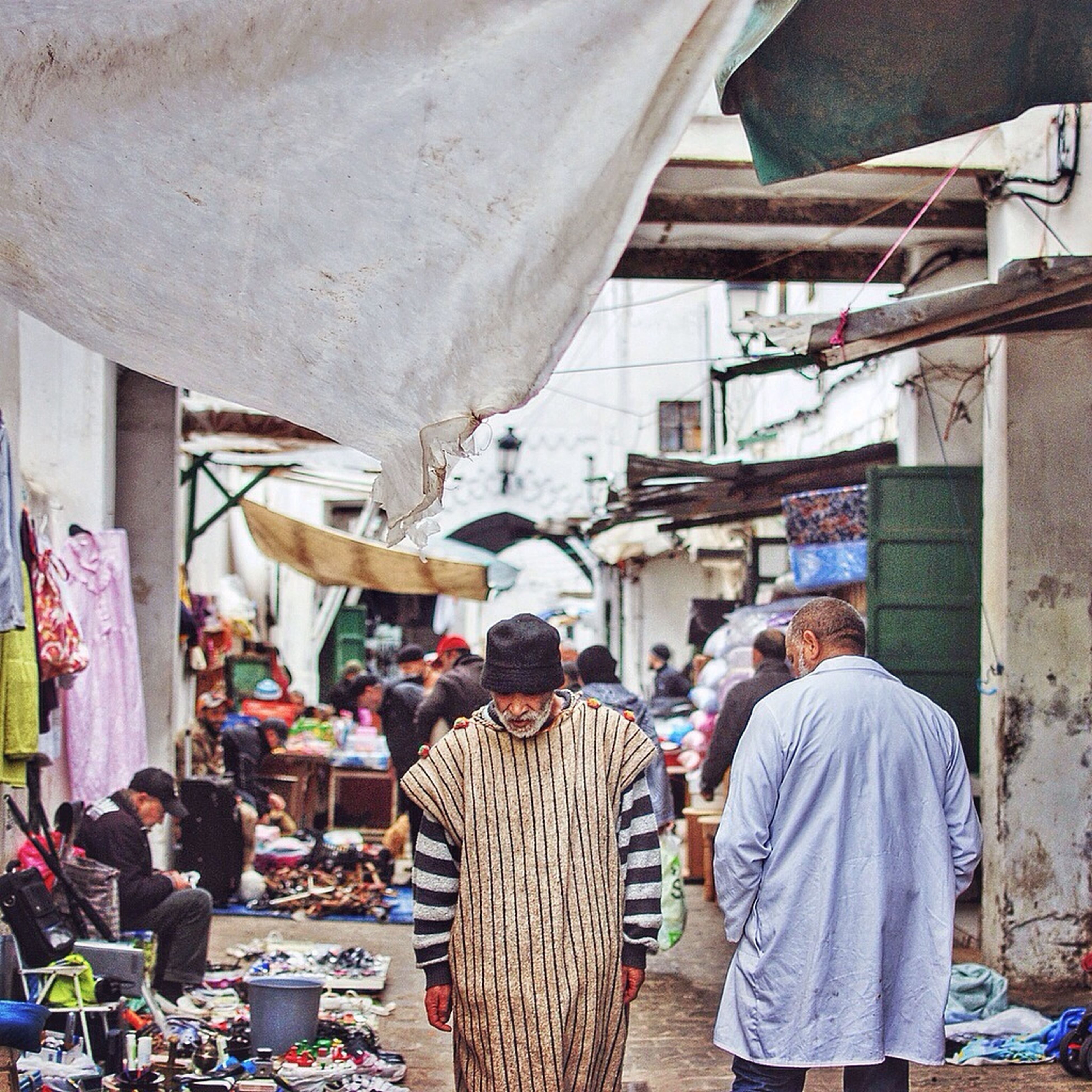 men, person, architecture, built structure, lifestyles, building exterior, market, large group of people, rear view, market stall, walking, leisure activity, occupation, casual clothing, city life, street, retail, shopping, working