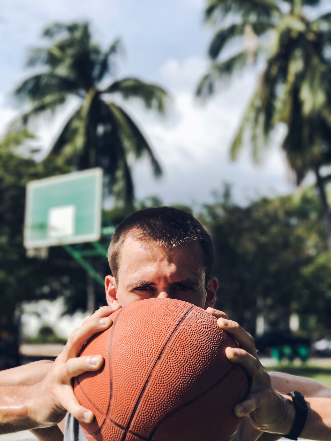Adult Adults Only Ball Basketball - Sport Basketball Court Basketball Player Close-up Day Front View Headshot Healthy Lifestyle Holding One Man Only One Person Only Men Outdoor Activity Outdoors Palm Tree People Playing Sport Sports Sportsman Tree Young Adult