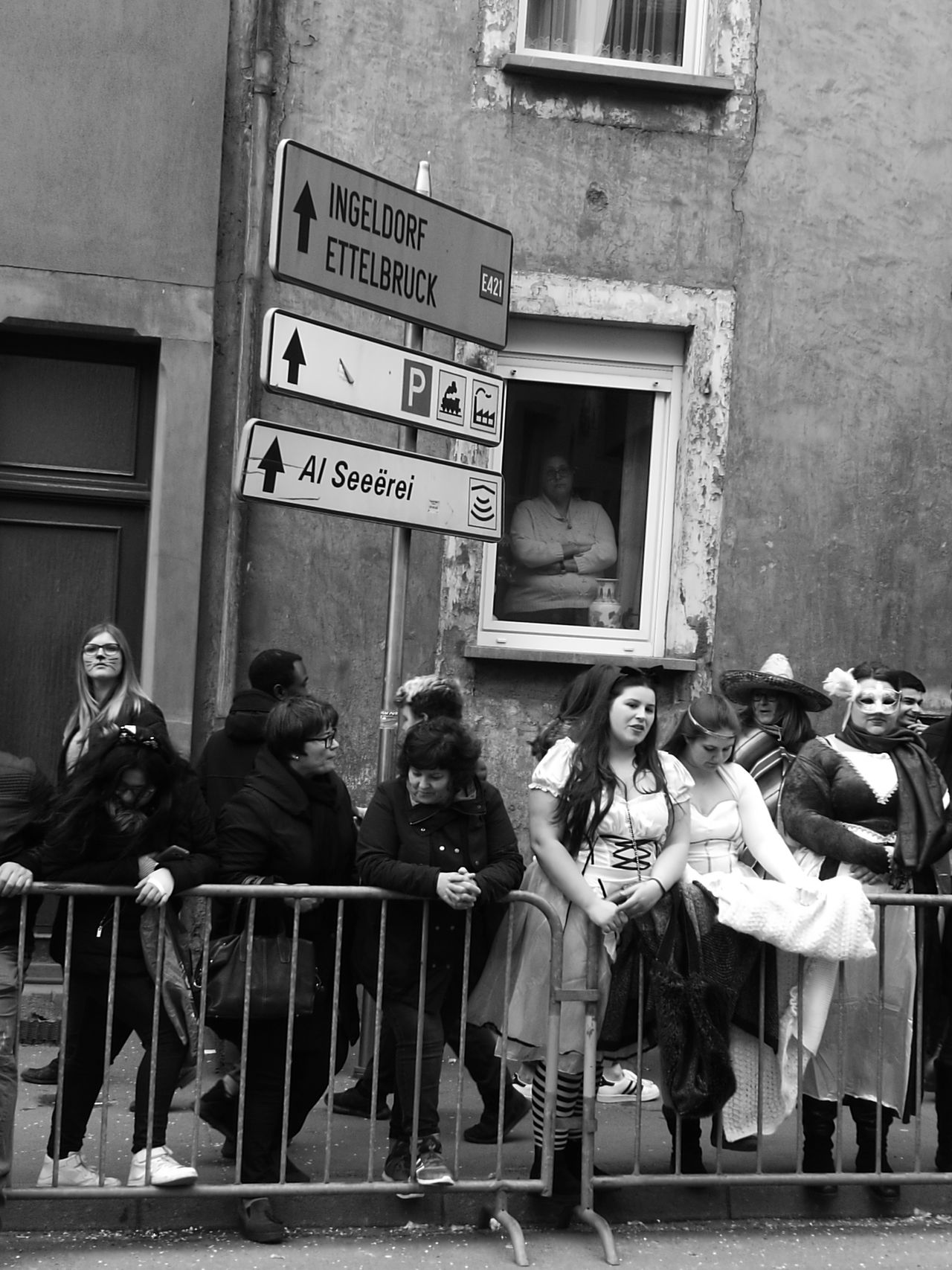 Carnival Crowds And Details Arts Culture And Entertainment Women Adult Adults Only Building Exterior People Outdoors Full Length City Architecture Day Men Togetherness Carnival In Luxembourg Diekirch Women In The Window Watching Luxembourg Streetphotography Luxembourg_Collection Black And White Photography Carnival