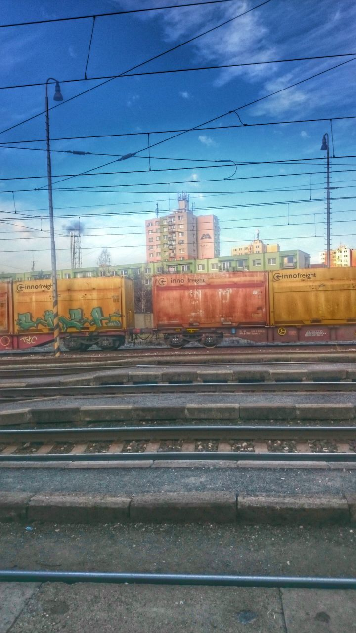 railroad track, rail transportation, transportation, cable, power line, train - vehicle, electricity pylon, public transportation, mode of transport, sky, electricity, power supply, no people, connection, railway track, shunting yard, outdoors, day, built structure, freight transportation, architecture, railway signal, railway, building exterior, locomotive, city