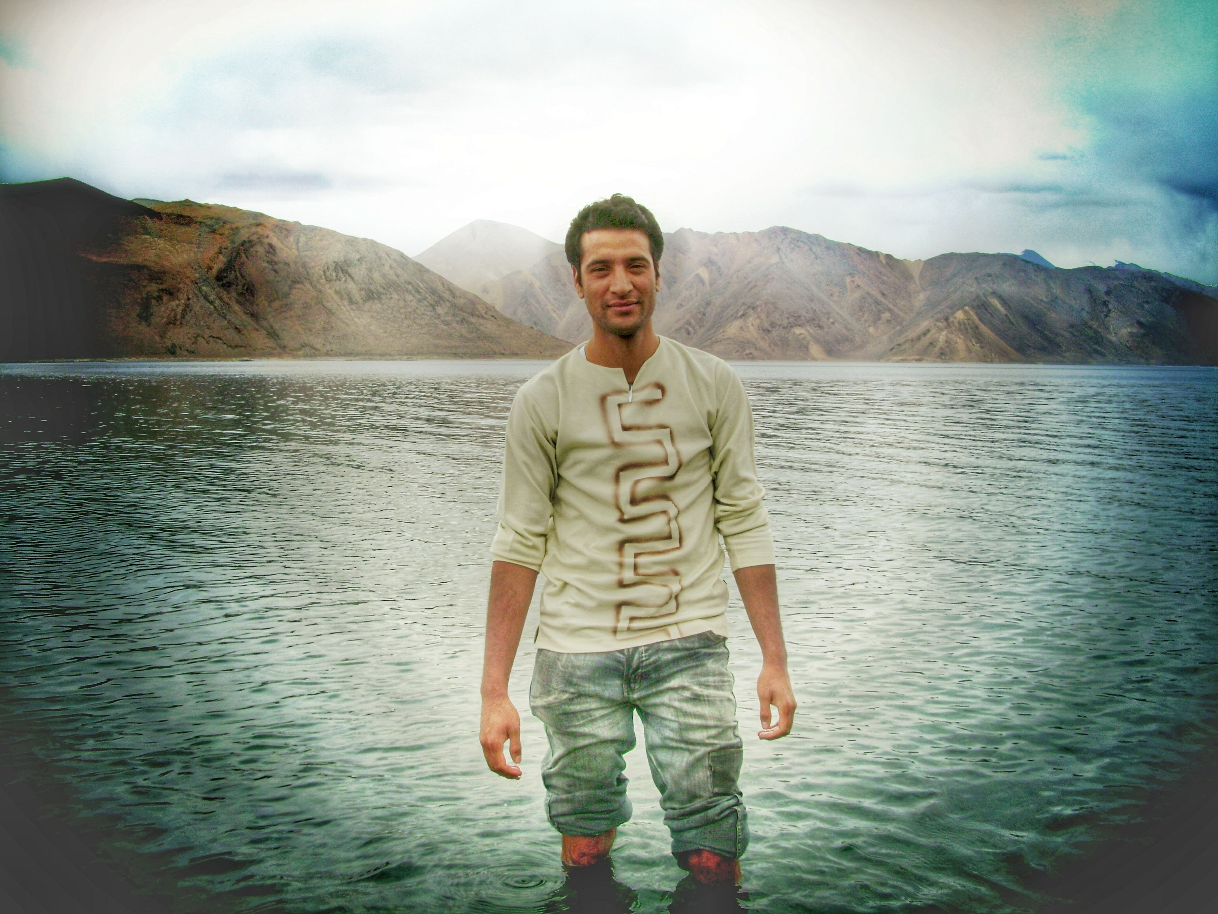 water, lifestyles, casual clothing, mountain, standing, person, young adult, leisure activity, looking at camera, three quarter length, sky, portrait, front view, young men, lake, full length, tranquility, scenics