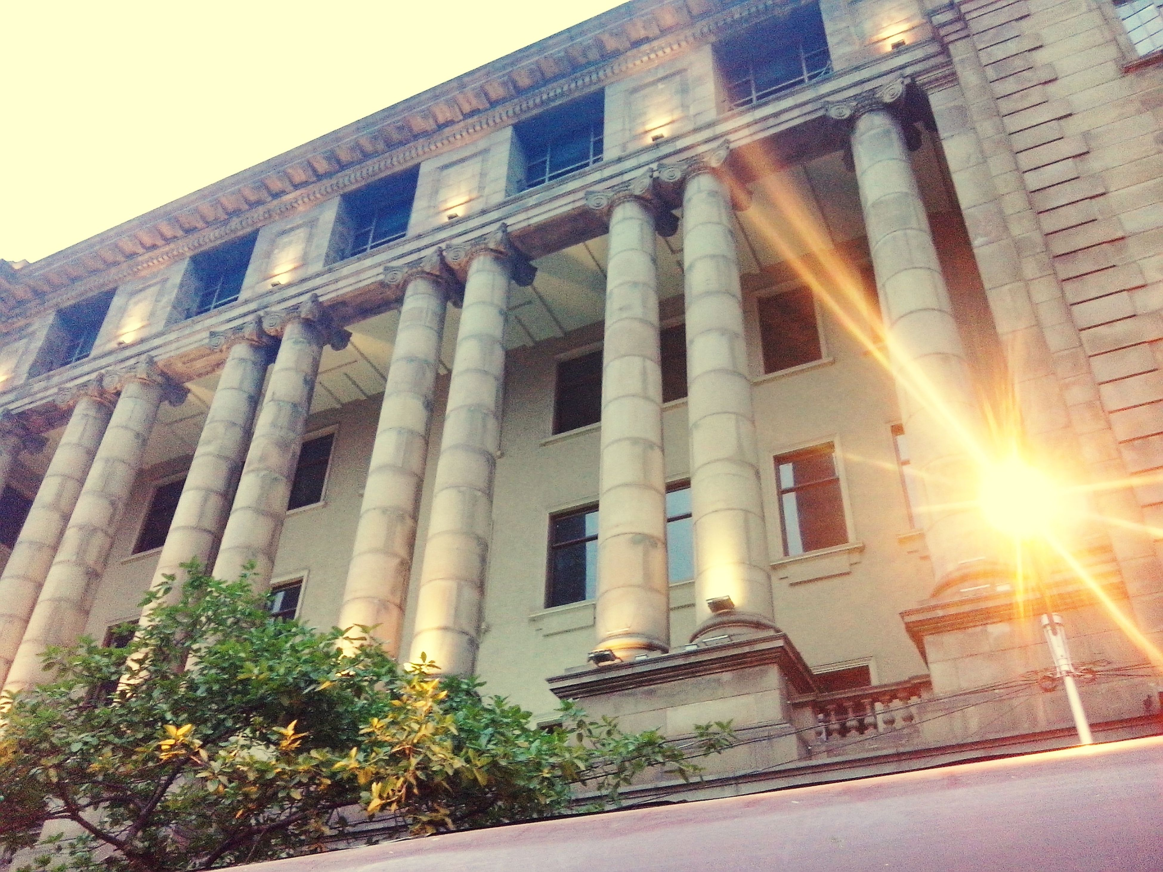 architecture, built structure, building exterior, low angle view, sun, sunlight, sunbeam, city, sky, lens flare, history, building, facade, architectural column, travel destinations, famous place, outdoors, tree, day, window