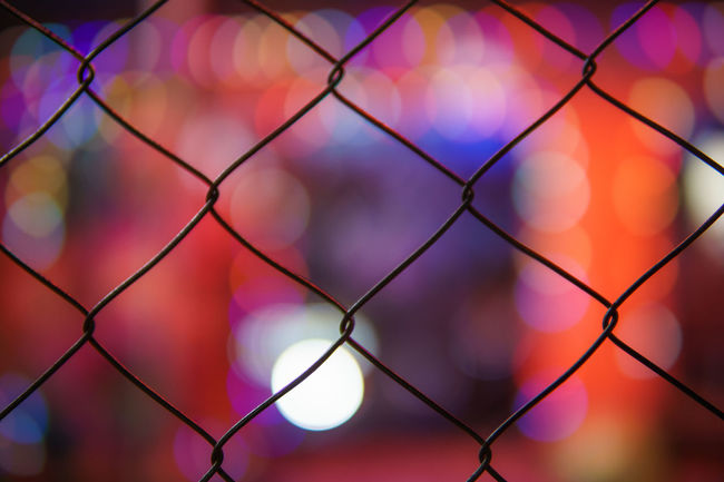 Fence Chainlink Fence Close-up Safety Focus On Foreground Backgrounds Full Frame Outdoors Protection Chain Link Fence No People Tranquil Scene Bokeh Bokeh Lights Still Life Street Photography