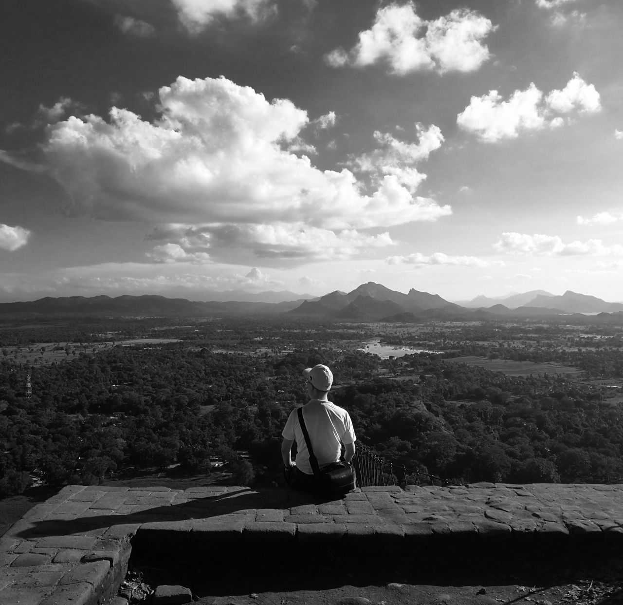 sitting, real people, mountain, one person, sky, nature, cloud - sky, day, outdoors, lifestyles, scenics, beauty in nature, men, full length, landscape, retaining wall, young adult, people
