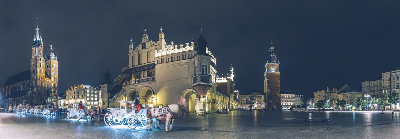 Long exposure wide panoramic view of the market square in the center of the old town of Krakow, Poland. Architecture Building Exterior Built Structure City City Life Cityscape Horse Carriage Illuminated Krakow Leisure Activity Night Outdoors Panoramic People Place Of Worship Poland Rynek Rynek Główny Square Tourism Travel Travel Destinations Vacations