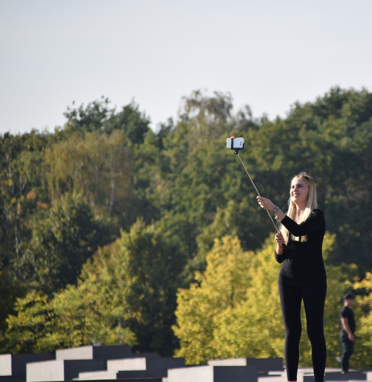Mobile Conversations One Woman Only Mobile Mobile Photography Berlin Tourist Selfıe Selfie Stick Standing Wearing Black Blonde Blonde Girl Sunny Outdoors