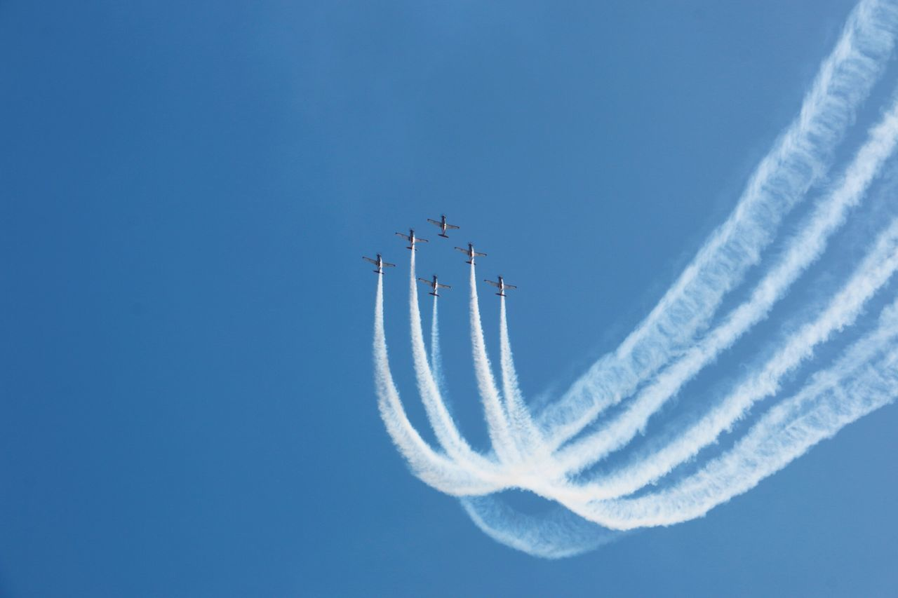 vapor trail, airplane, airshow, speed, teamwork, flying, smoke - physical structure, transportation, low angle view, sky, blue, mode of transport, air vehicle, fighter plane, arrangement, motion, mid-air, military airplane, day, outdoors, aerobatics, no people, formation flying, performance, clear sky, stunt, air force
