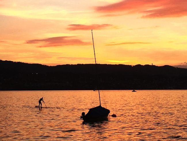 Sunset Dusk Water Waterfront Orange Color Dramatic Sky Boat Sailboat Standuppaddle Scenics Beauty In Nature Tranquility Tranquil Scene Herrliberg Switzerland