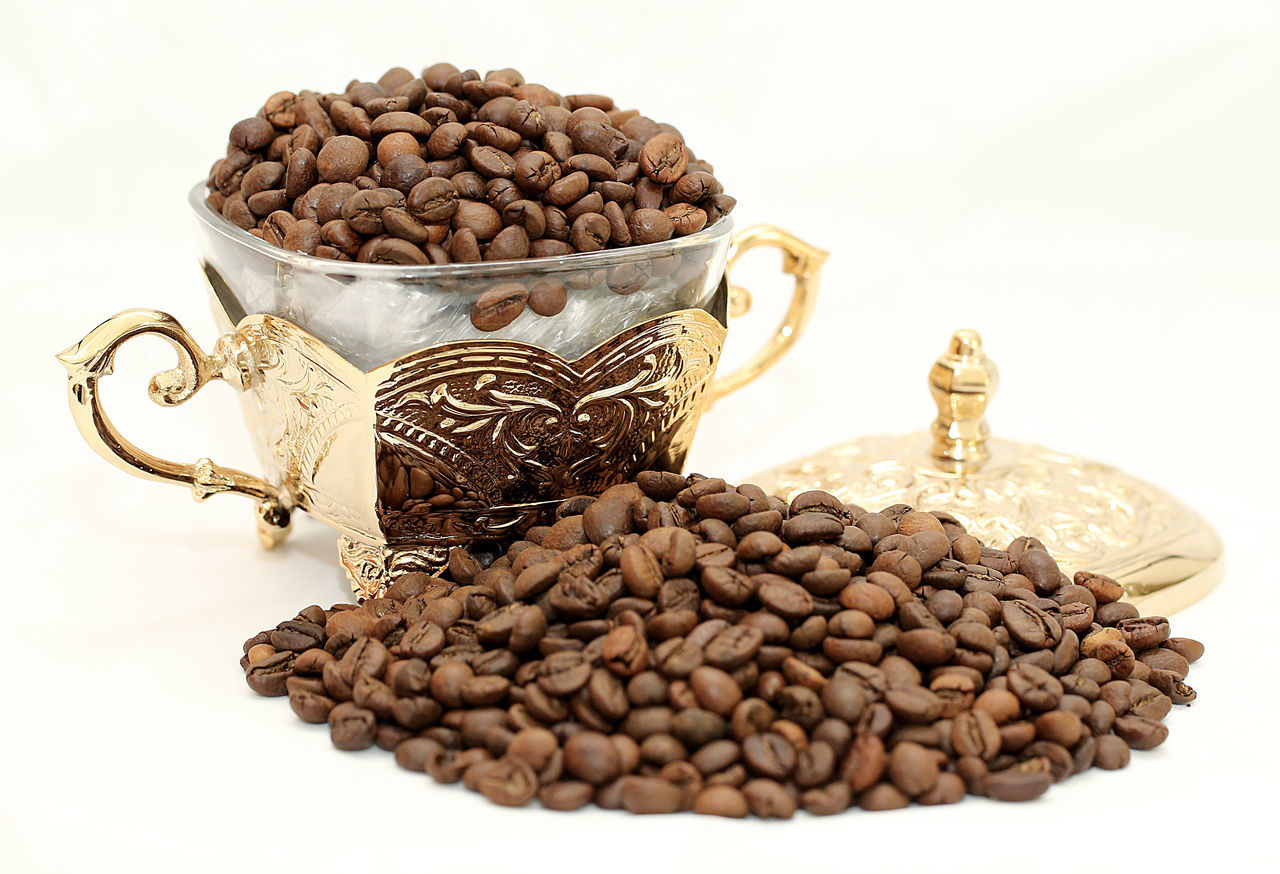 Close-Up Of Roasted Coffee Beans In Container Over White Background