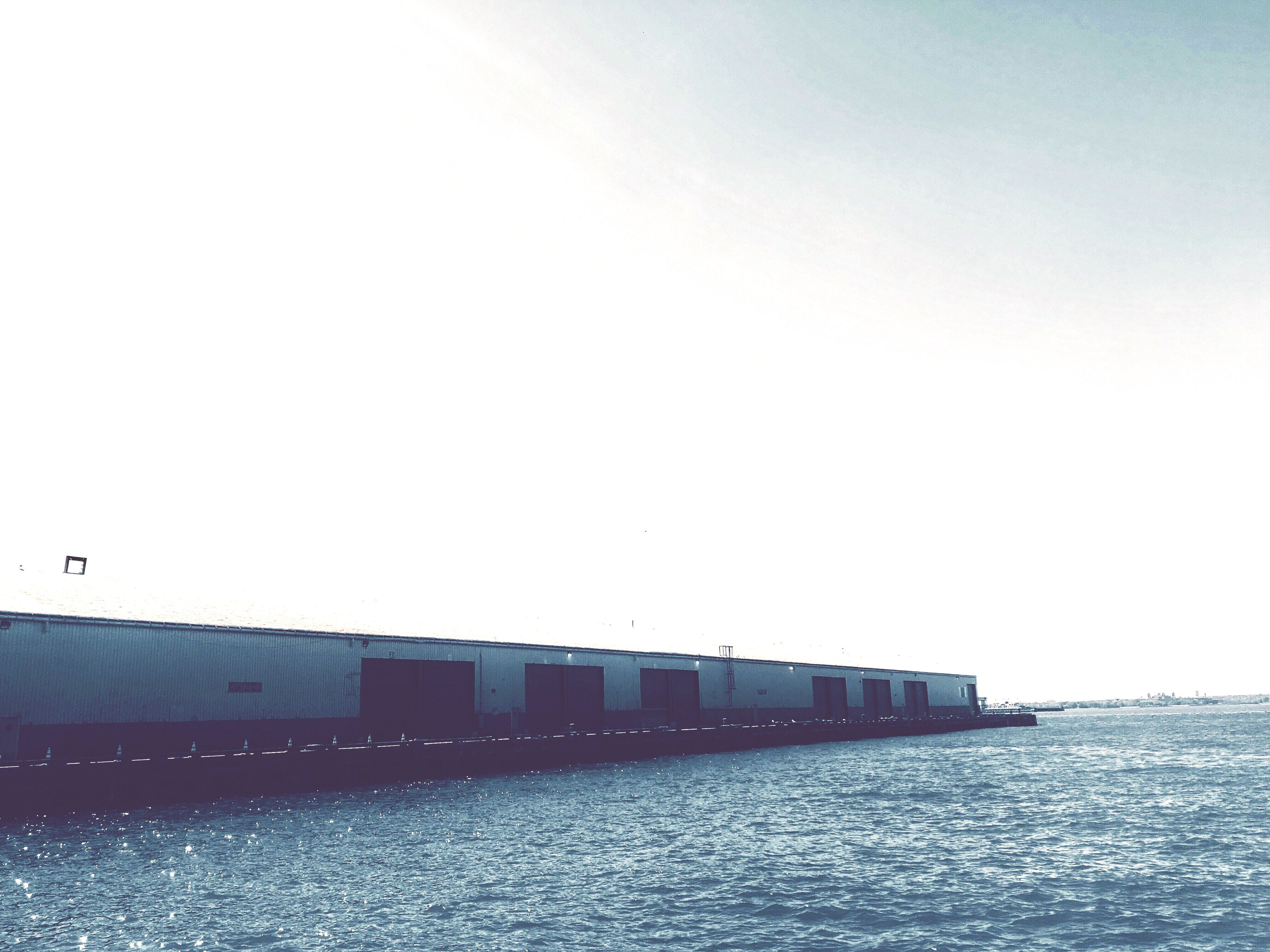 waterfront, architecture, clear sky, water, building exterior, built structure, copy space, sea, calm, tranquil scene, tranquility, day, outdoors, scenics, surface level, no people, ocean, solitude
