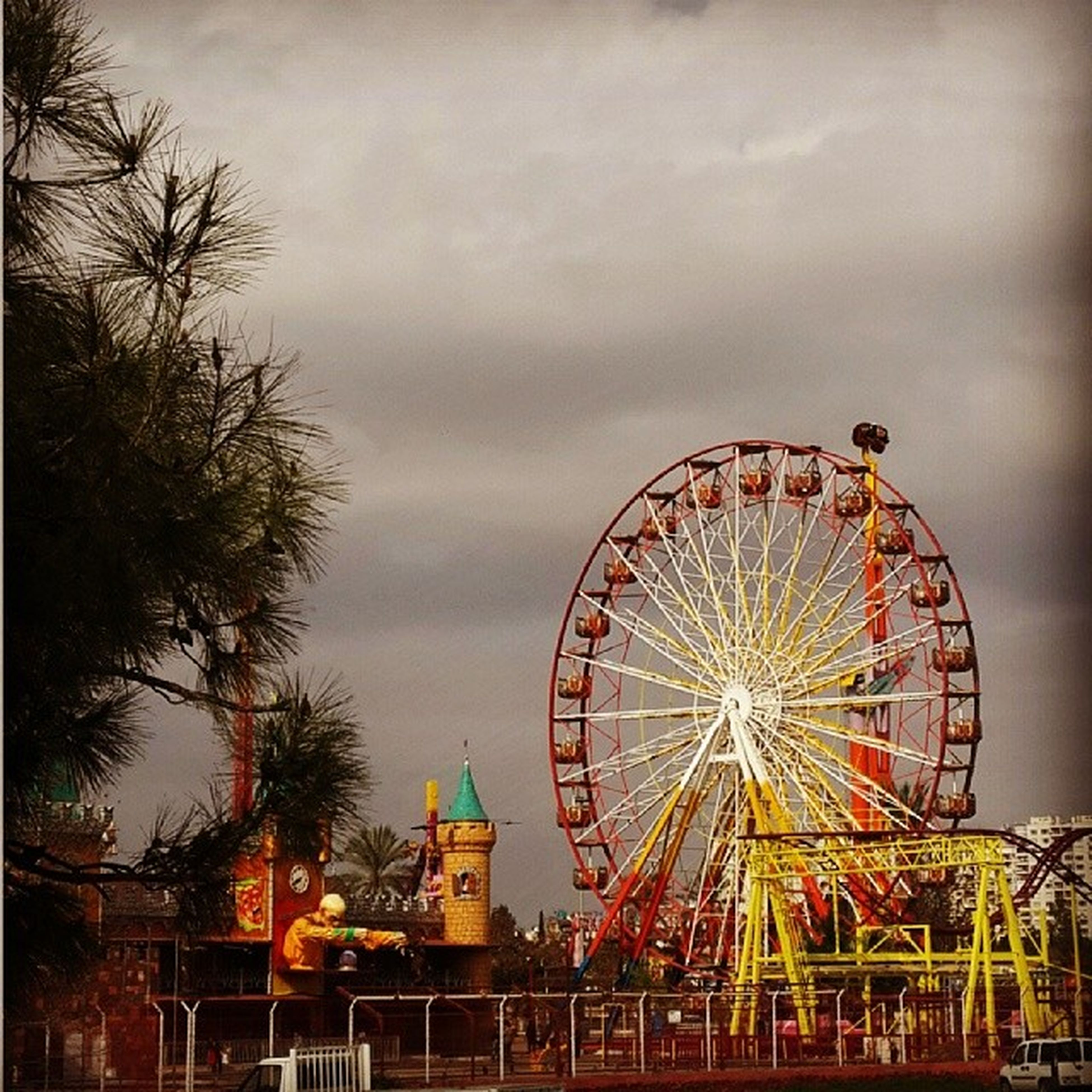 amusement park, ferris wheel, amusement park ride, sky, arts culture and entertainment, built structure, low angle view, cloud - sky, architecture, tree, cloudy, building exterior, metal, cloud, outdoors, no people, day, dusk, large, overcast
