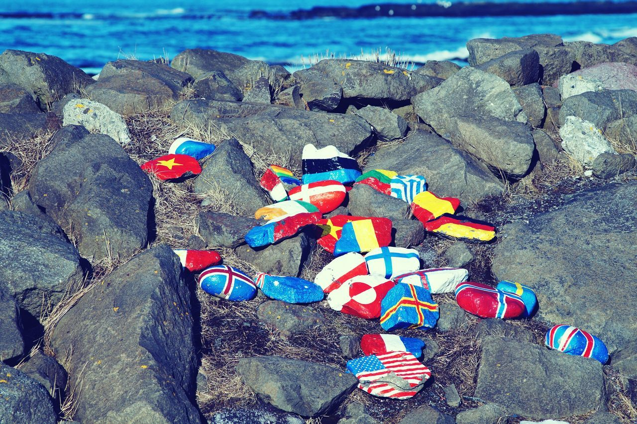 Flags Painted On Rocks At Beach
