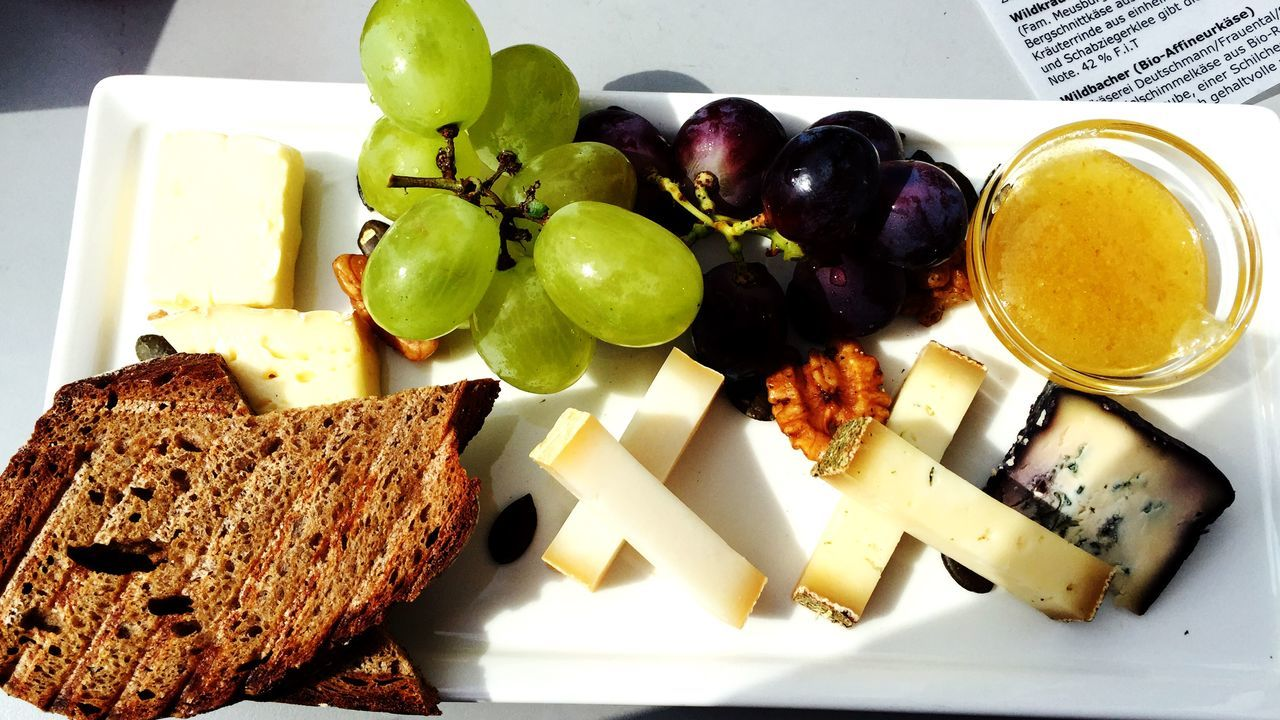 High Angle View Of Cheese With Bread And Grapes On Plate