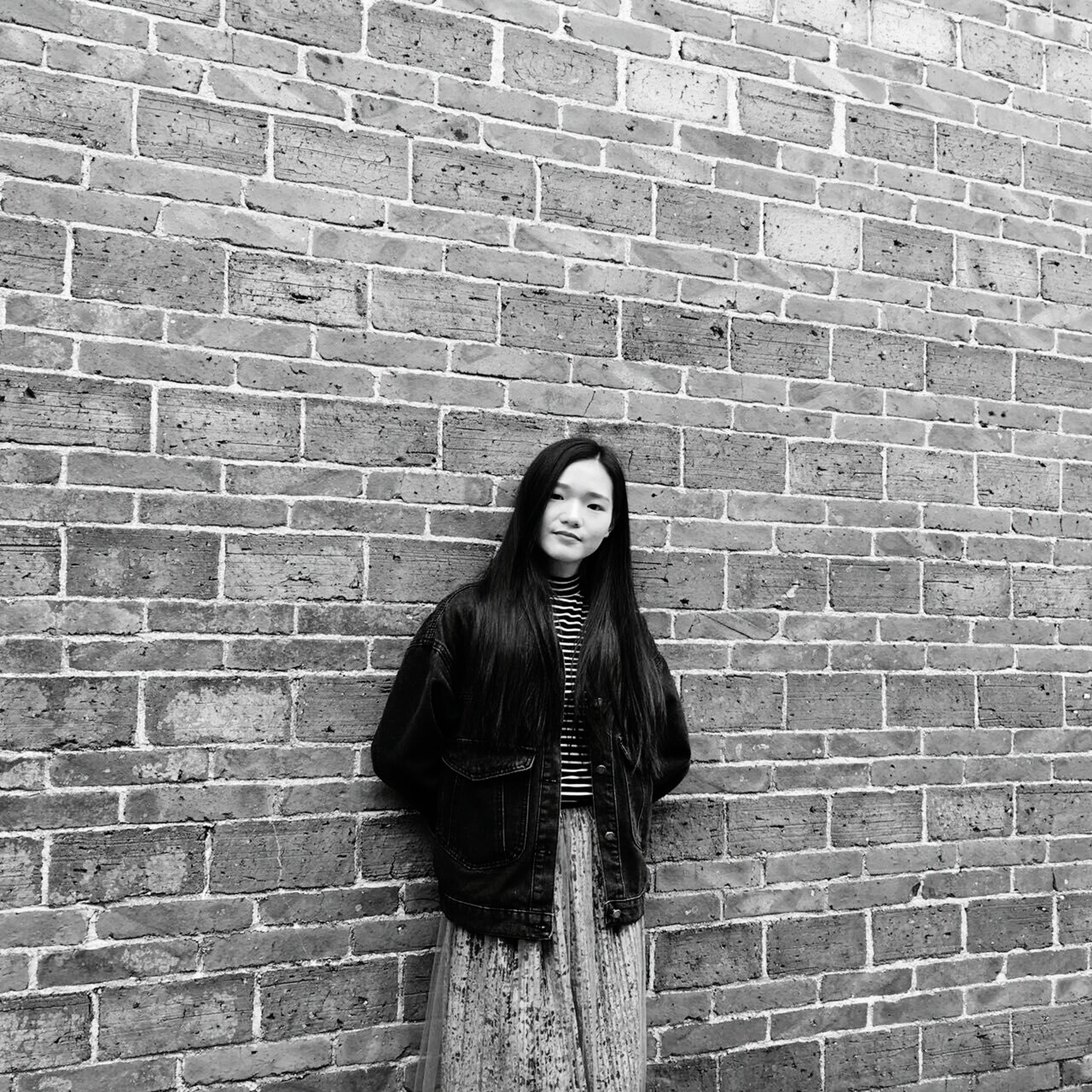 brick wall, one person, standing, real people, young adult, young women, adults only, day, outdoors, one woman only, people, adult, only women
