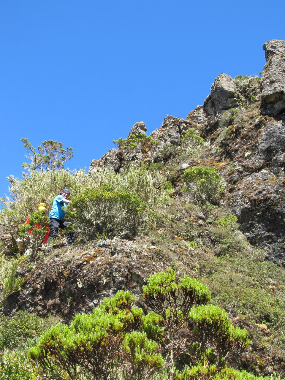Low Angle View Of Hiker Climbing On Mountain Against Clear Blue Sky