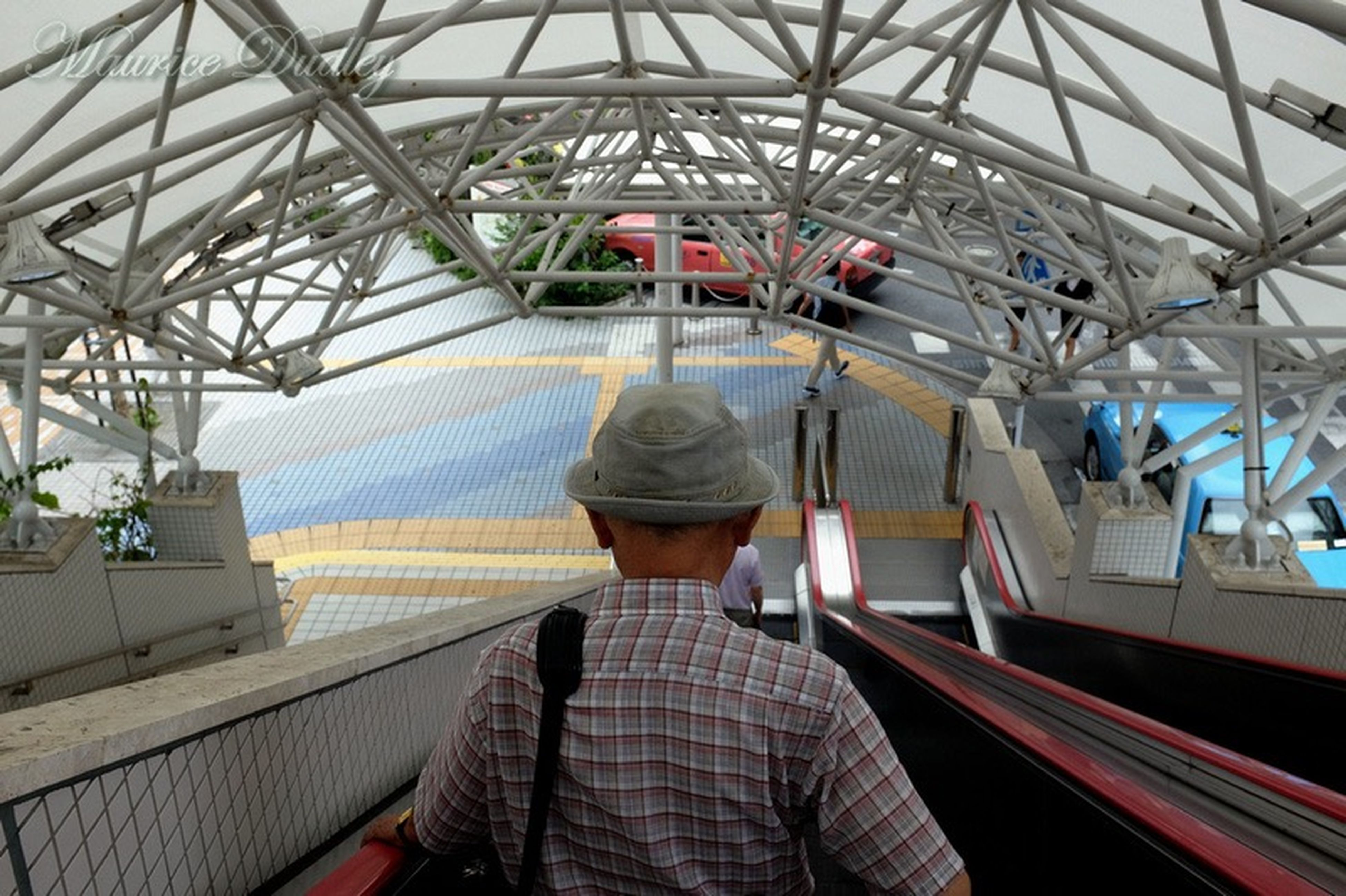 lifestyles, men, person, leisure activity, rear view, transportation, indoors, architecture, built structure, walking, railing, travel, escalator, standing, incidental people, city life, ceiling, full length