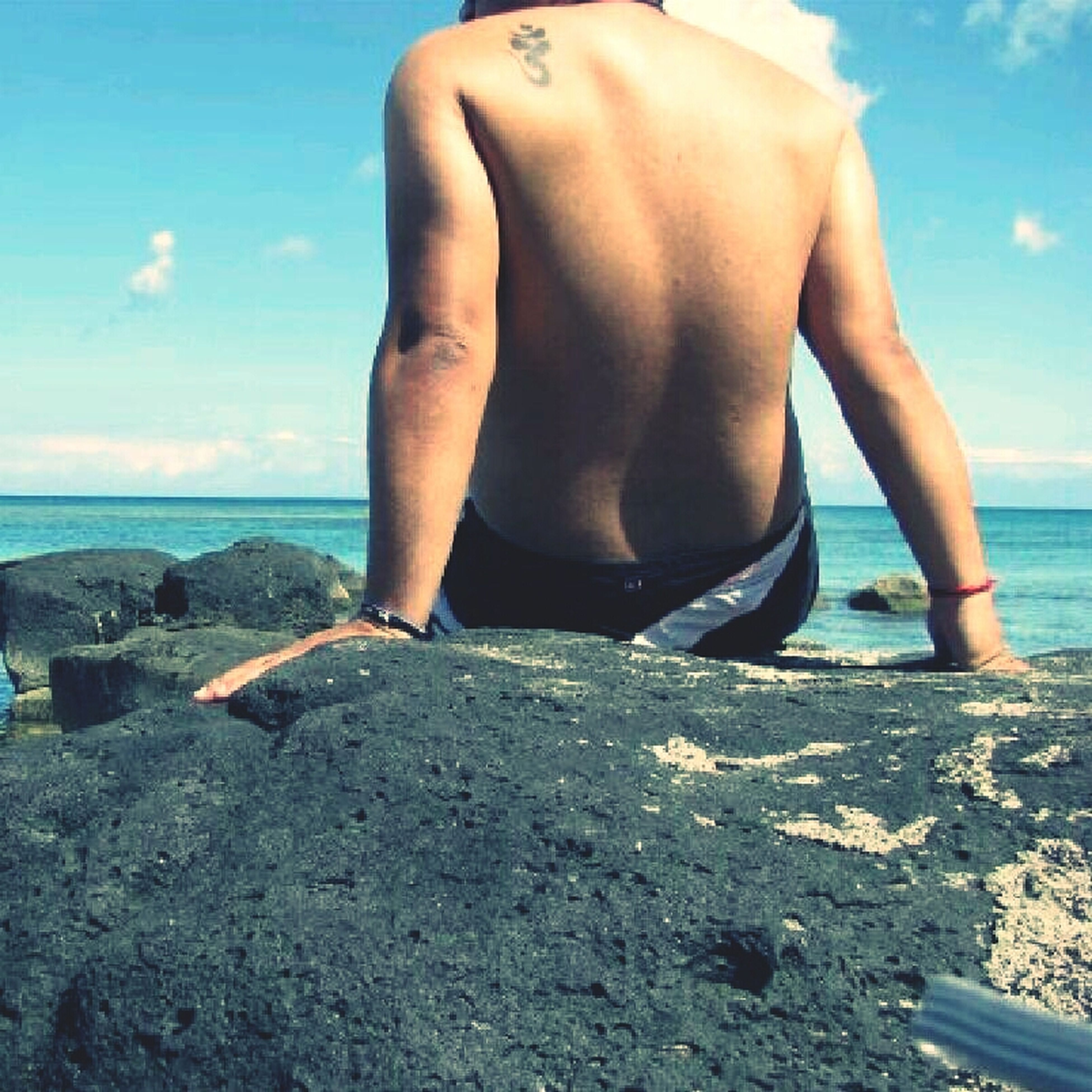 sea, beach, horizon over water, water, sky, shore, lifestyles, leisure activity, person, standing, rock - object, vacations, low section, sand, scenics, rear view, tranquility, nature