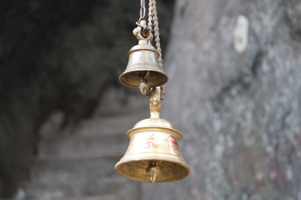 bell, focus on foreground, no people, gold colored, outdoors, close-up, religion, spirituality, hanging, day, low angle view, architecture, place of worship, built structure, building exterior