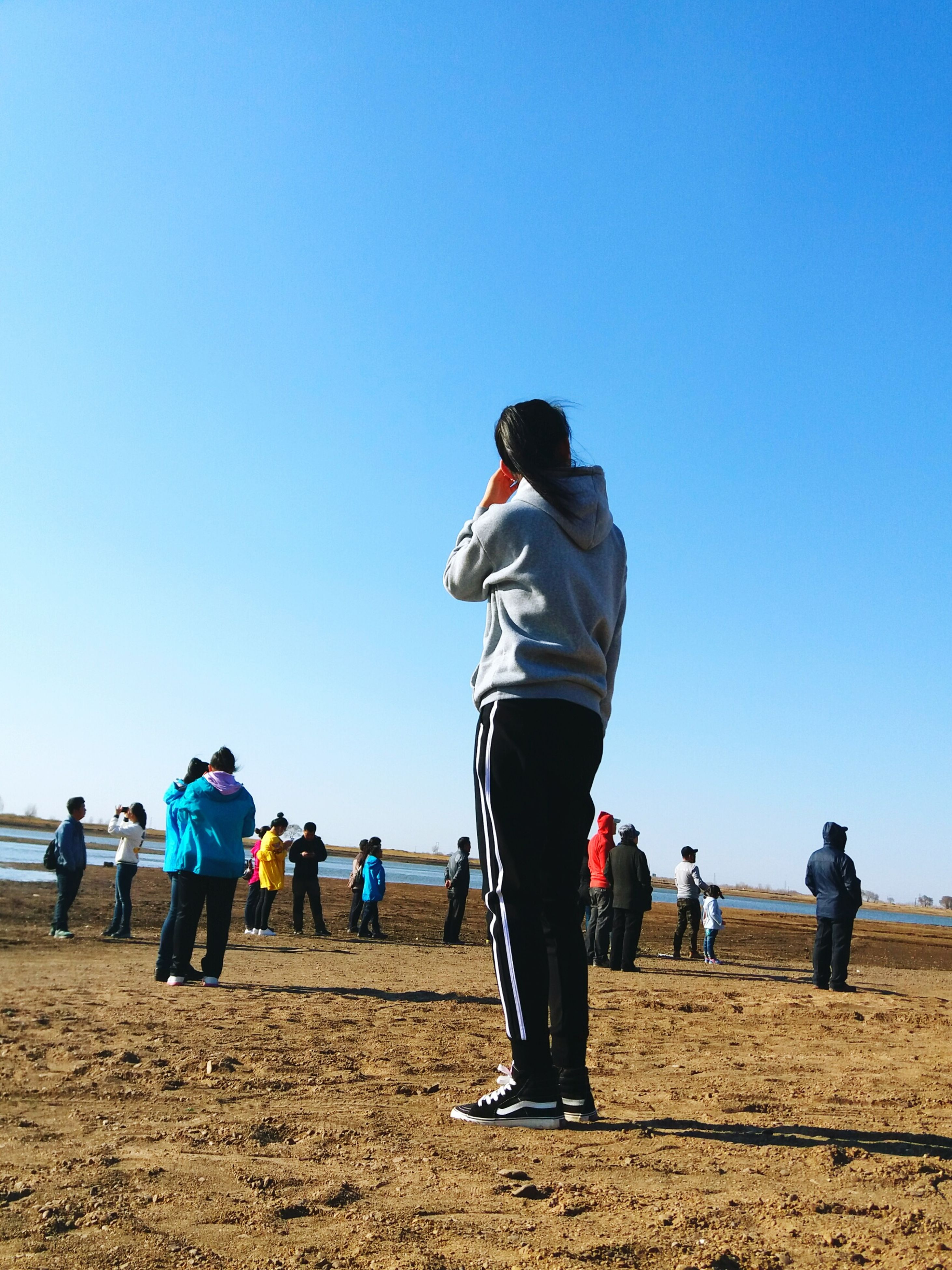 clear sky, real people, blue, leisure activity, lifestyles, outdoors, men, sport, day, sky, low angle view, adults only, beach, people, togetherness, adult, only men