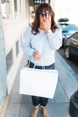 Holiday Shopping Small Business Adult Casual Clothing Customer  Day Front View Leisure Activity Lifestyles Looking At Camera Mature Women Older Woman One Person Outdoors People Portrait Real People Shopping Bag Spend Vertical Women