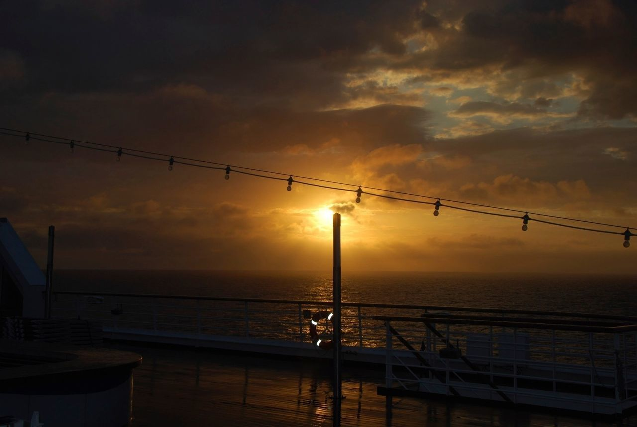 sunset, sea, sky, cloud - sky, silhouette, nature, orange color, scenics, no people, outdoors, beauty in nature, water, dusk, cable, horizon over water, architecture, technology