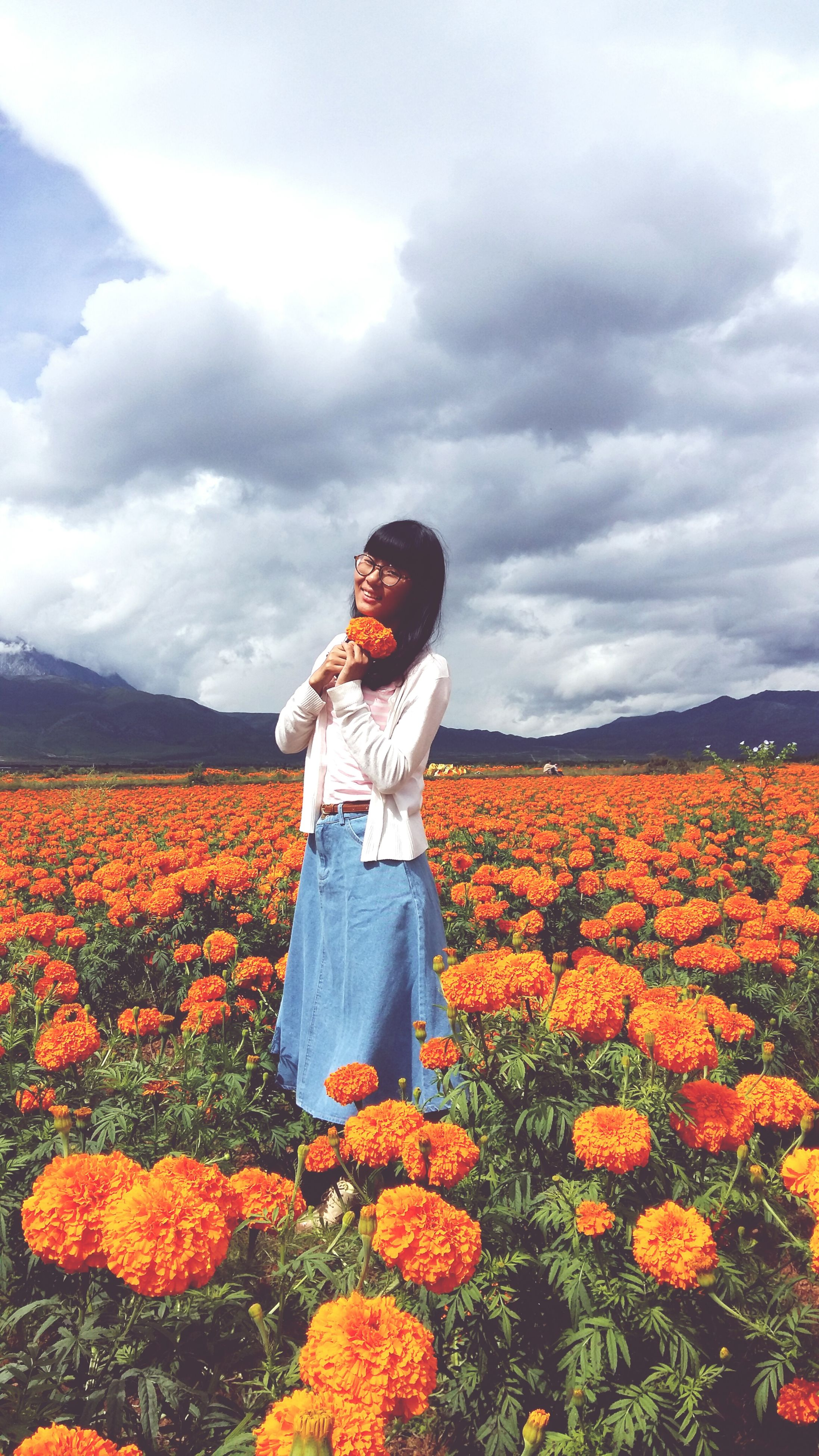 flower, sky, beauty in nature, cloud - sky, field, freshness, yellow, nature, growth, standing, plant, mountain, landscape, lifestyles, rural scene, agriculture, orange color, tranquility