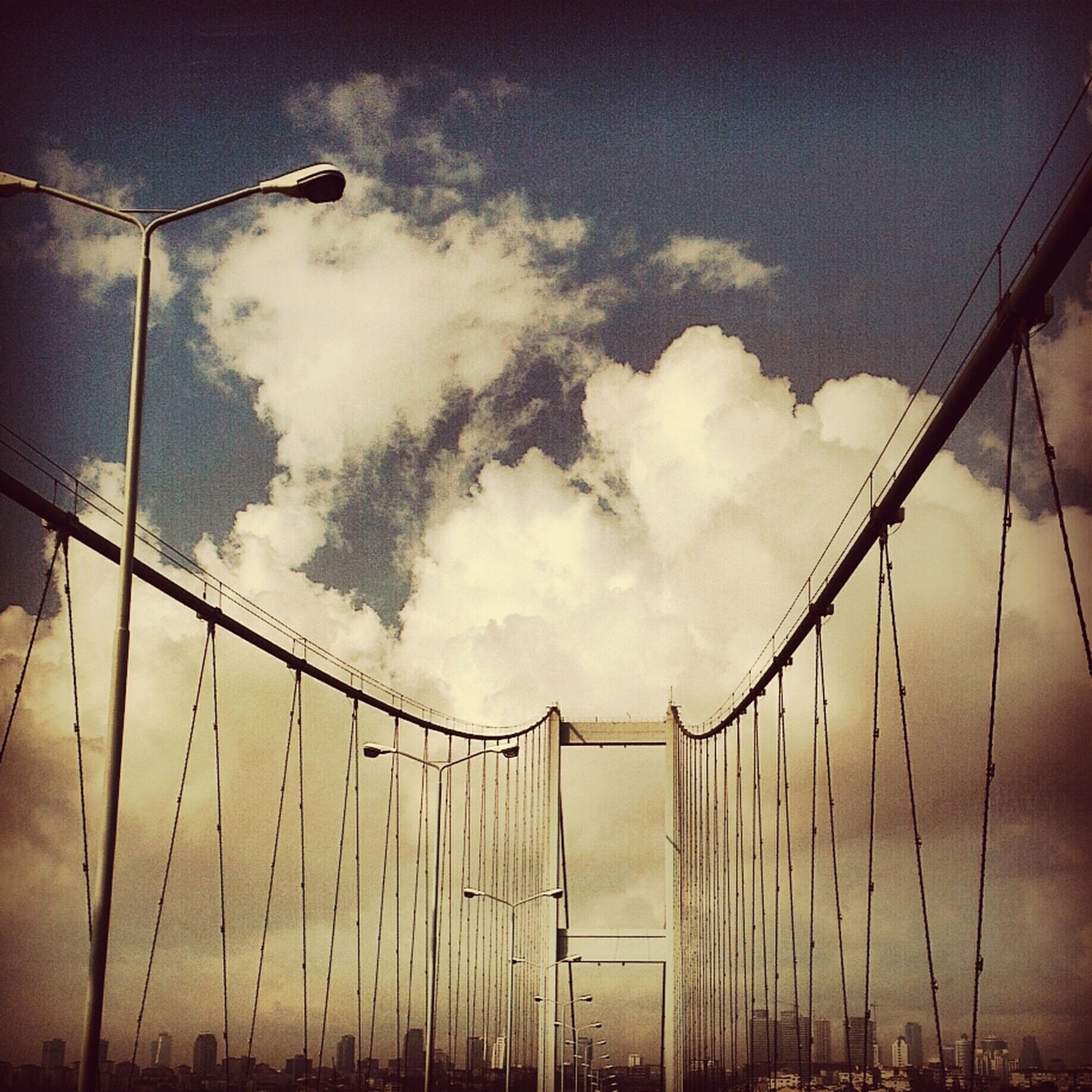 sky, connection, low angle view, bridge - man made structure, cloud - sky, built structure, engineering, architecture, cloudy, transportation, weather, suspension bridge, cloud, cable, outdoors, no people, dusk, overcast, bridge, cable-stayed bridge