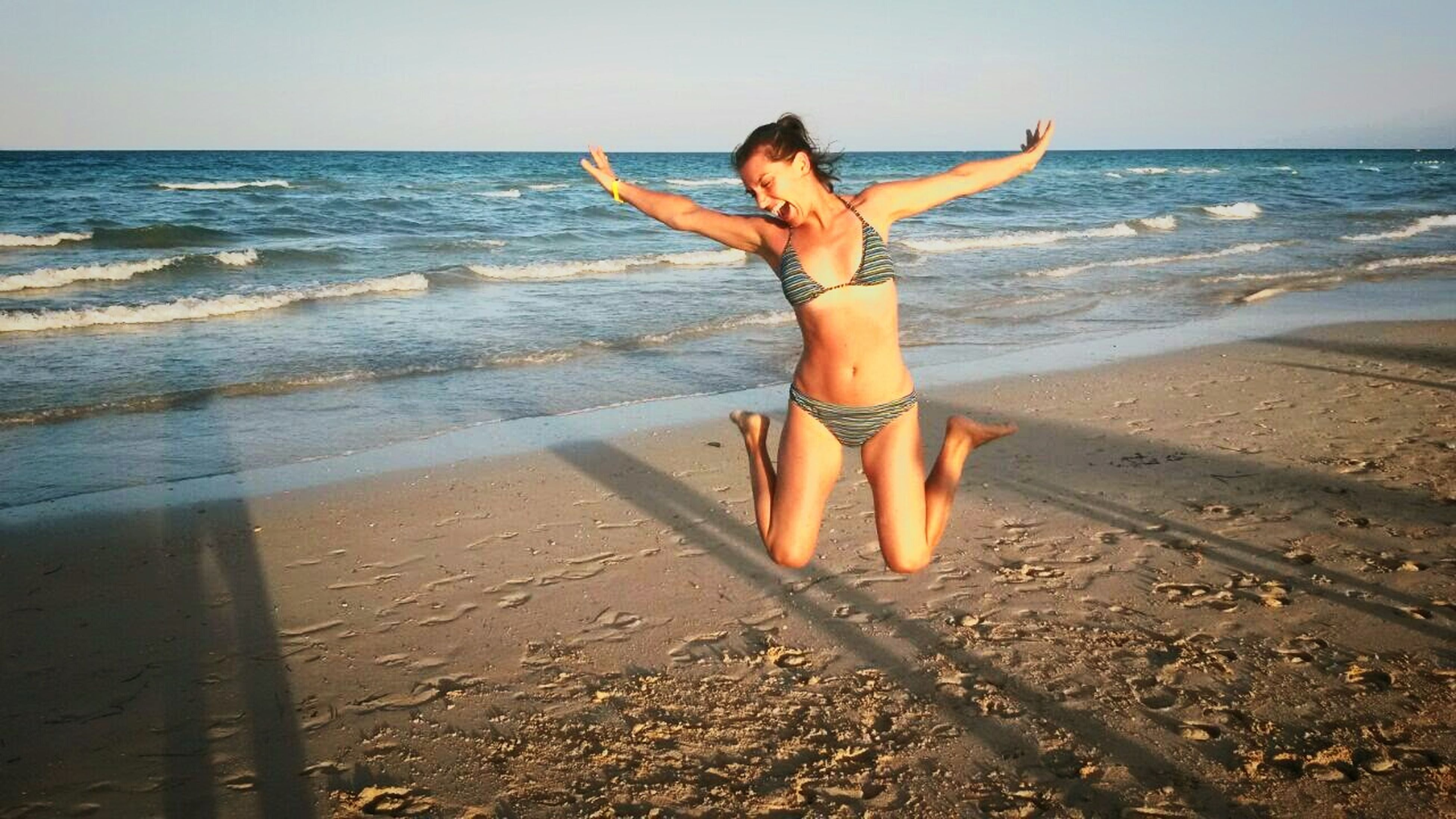 beach, sea, horizon over water, shore, sand, water, full length, leisure activity, vacations, lifestyles, young adult, person, summer, young women, sunlight, wave, sky, bikini