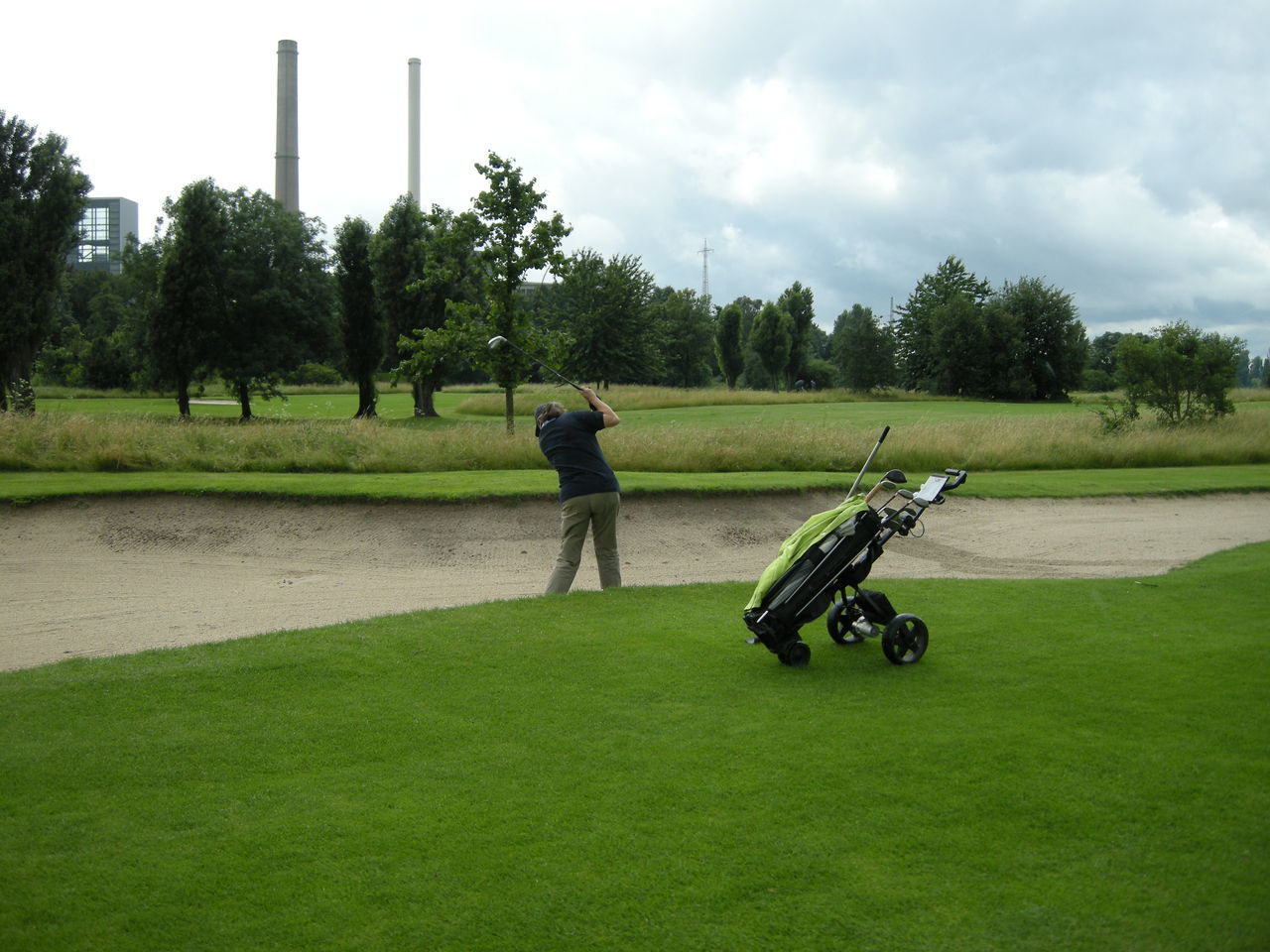 Rear View Of Person Playing Golf On Field Against Sky